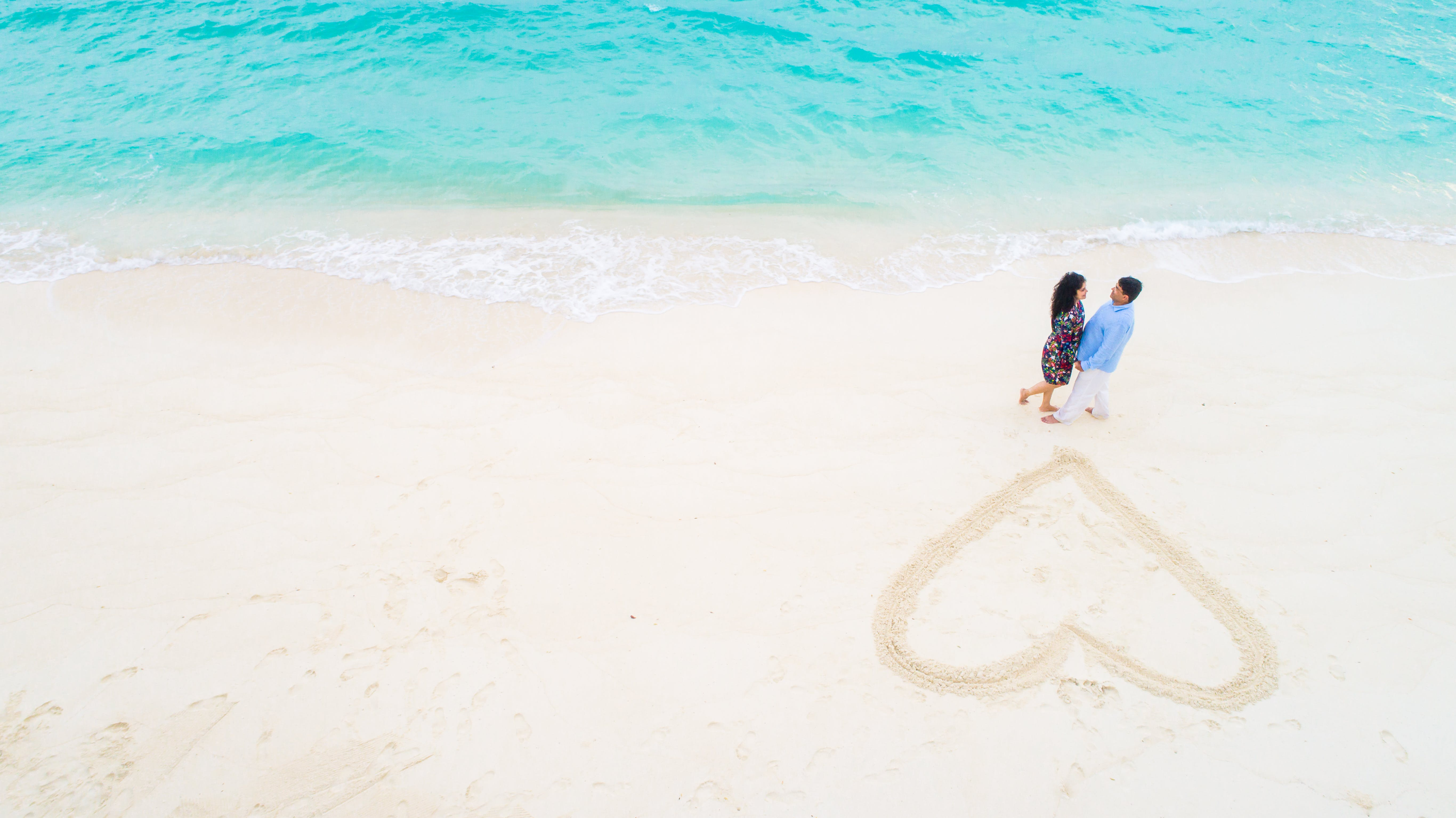 Two People Standing Beside Each Other Near Beach Shore