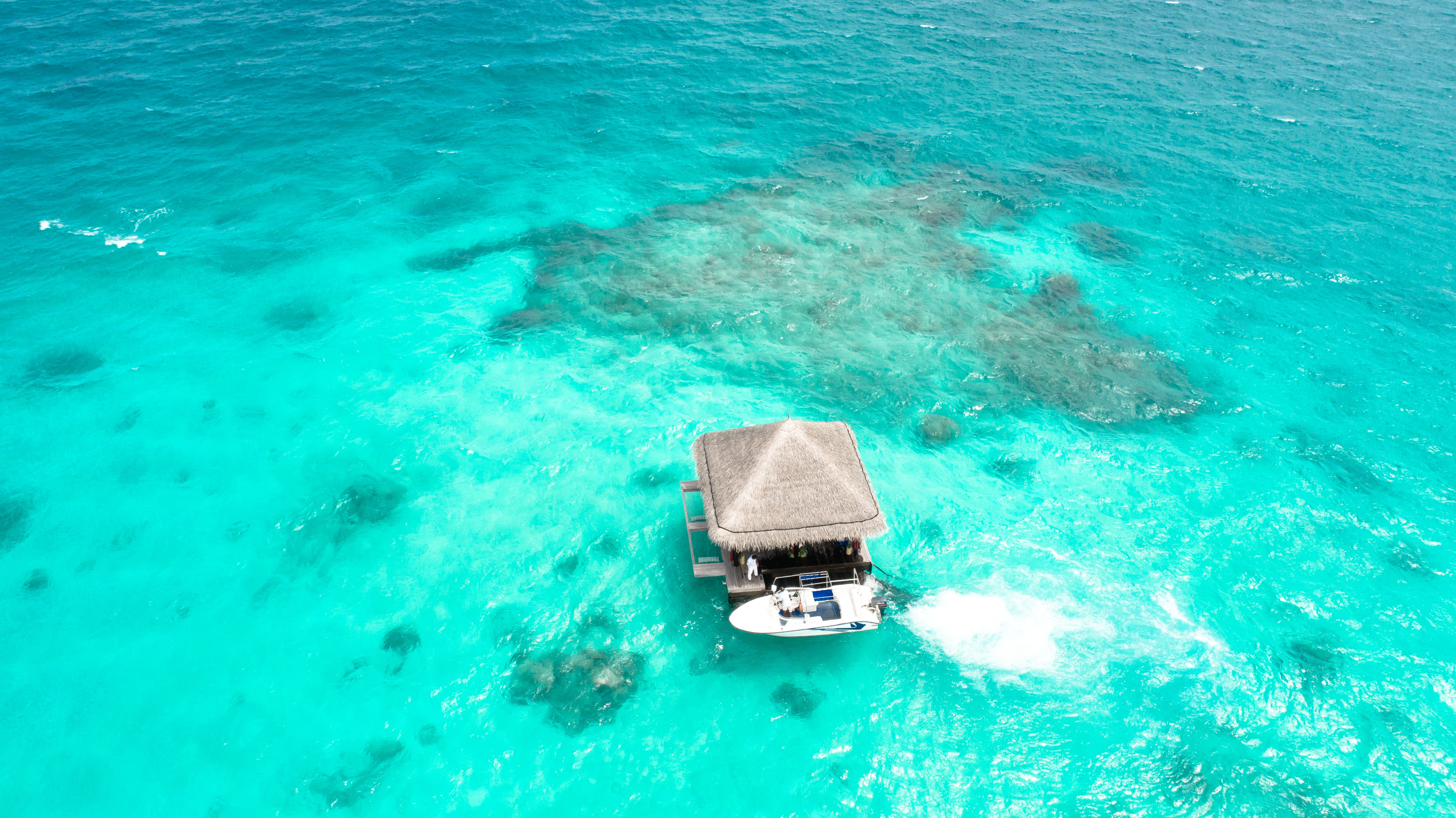 Aerial Photography of Brown House on Body of Water Beside Powerboat