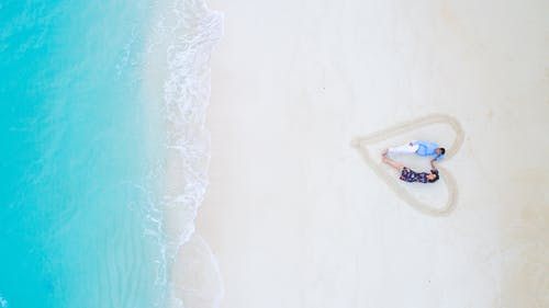 Man and Woman Lying on White Sand Near Sea Shore