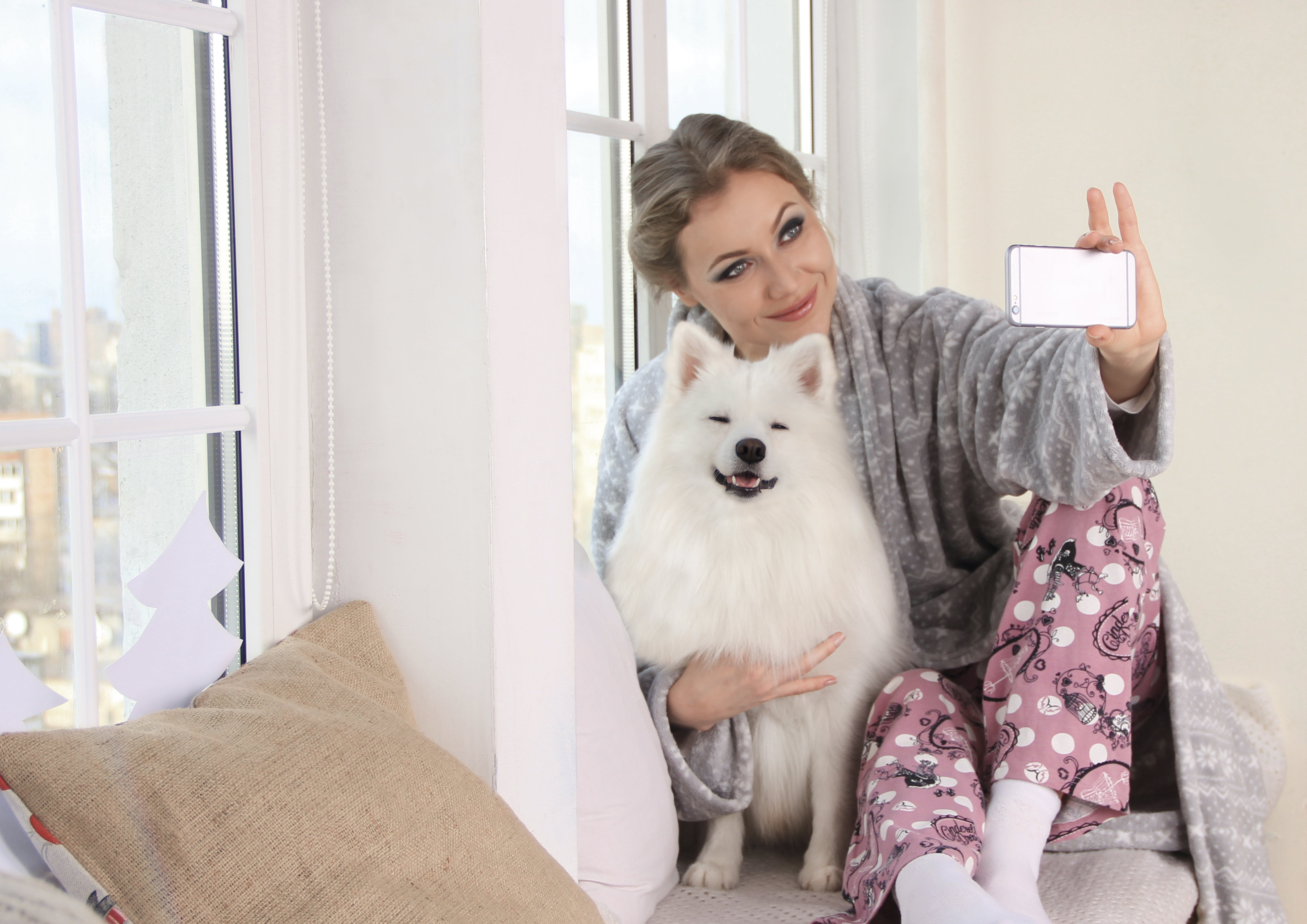 Woman Taking a Photo of Herself With White Dog