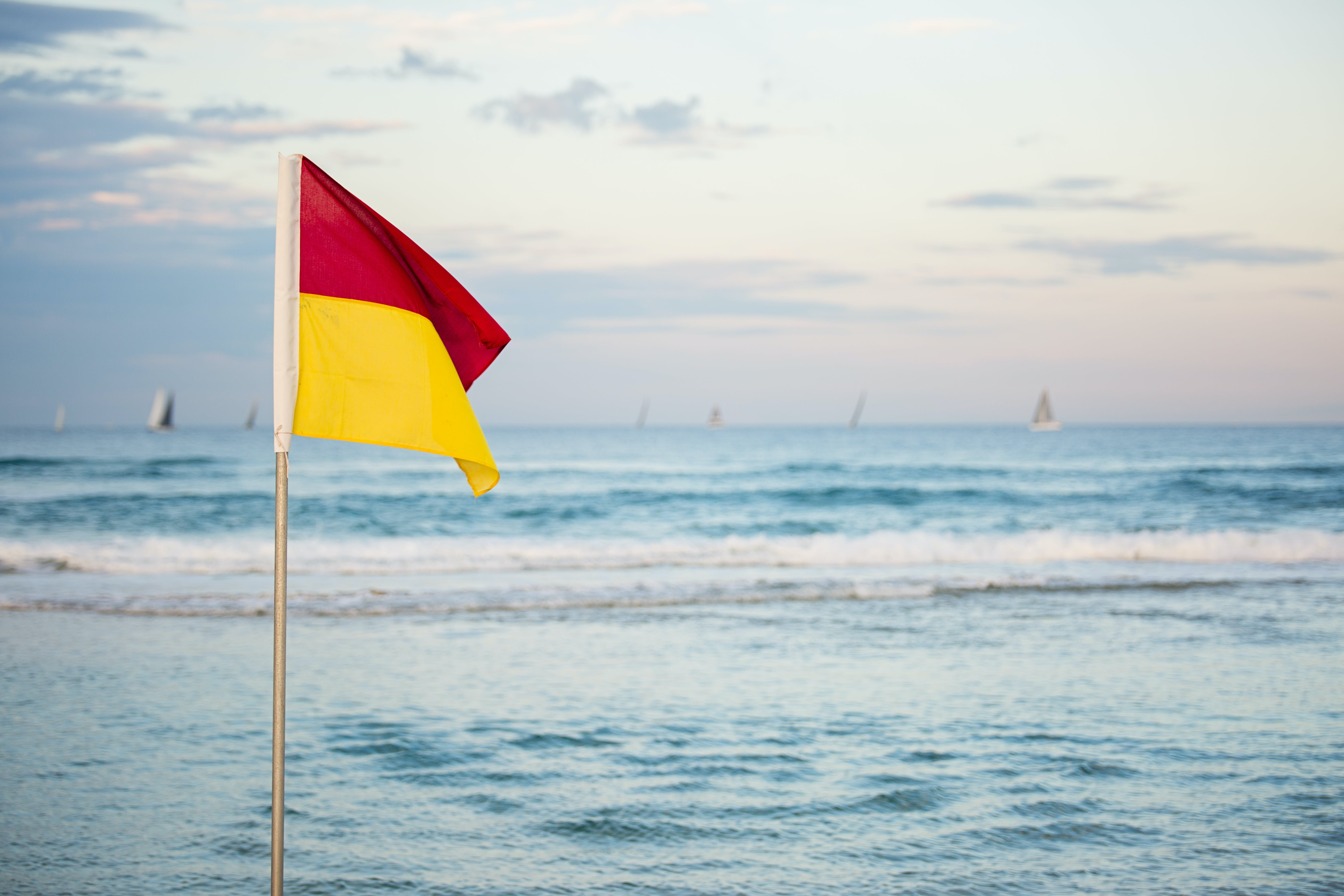 Red And Yellow Flag Standing Near Beach
