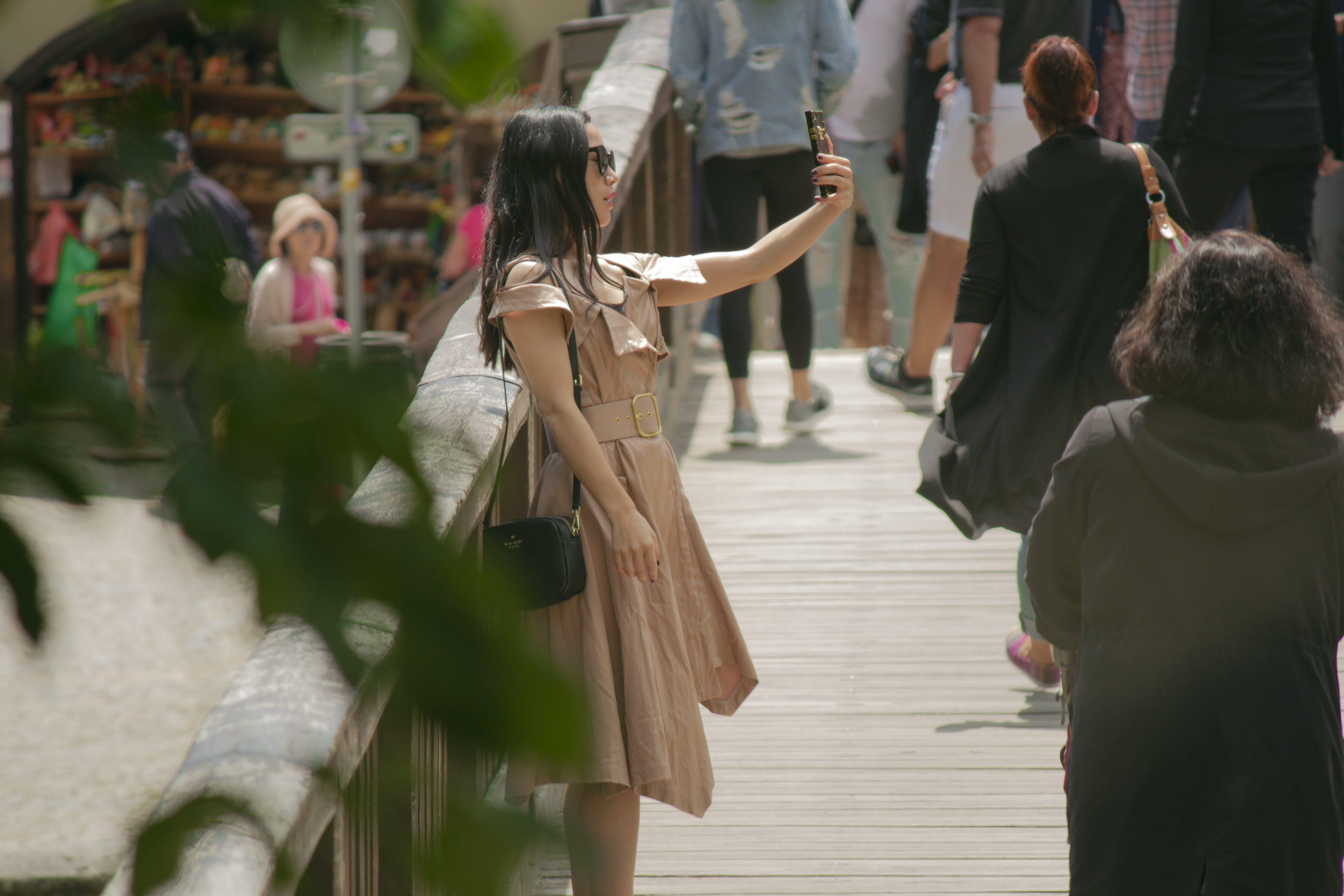 Woman Taking Selfie On Foot Bridge