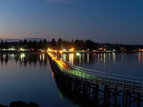 Free stock photo of causeway, city lights, night, sea