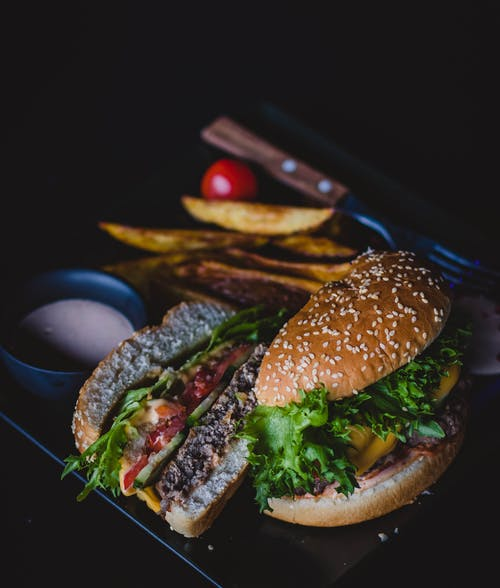Burger With Green Leafy Vegetable and Cheese on Black Plate