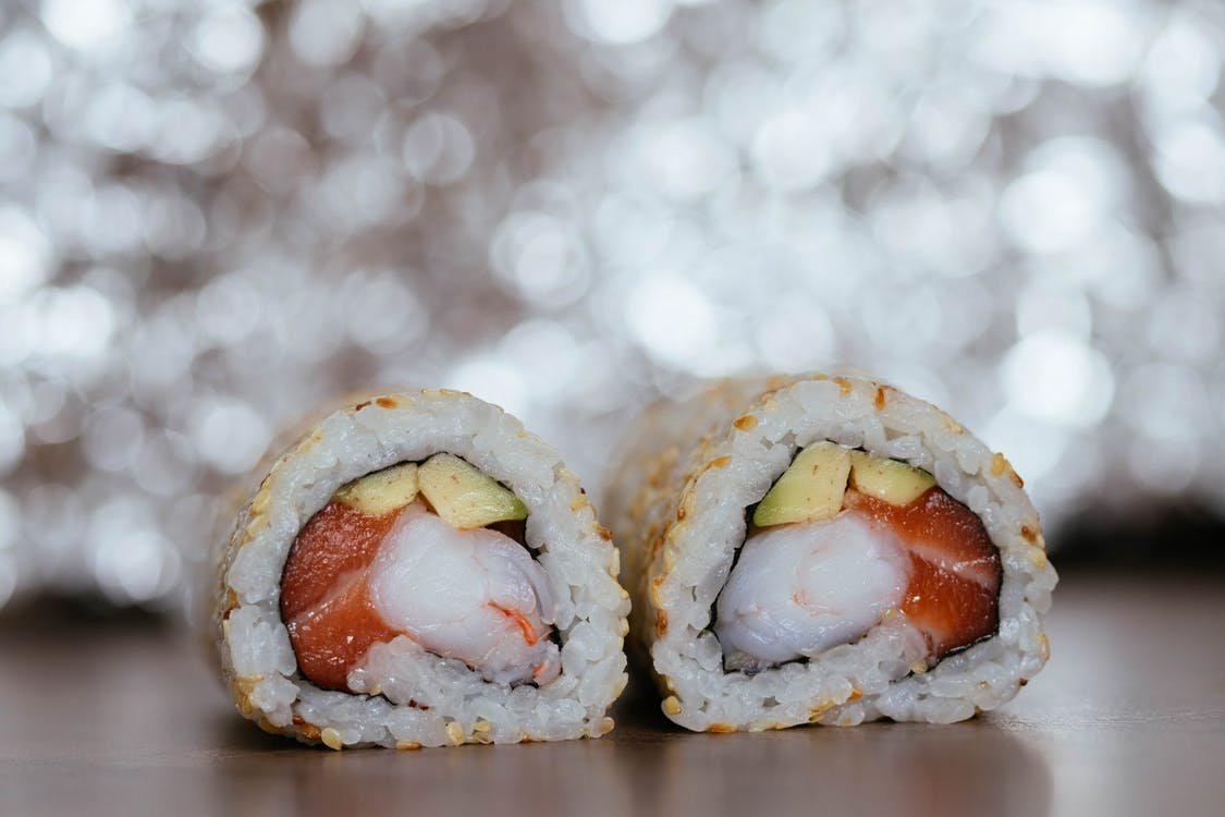 Focus Photography of Cooked Sushi on Brown Wooden Surface