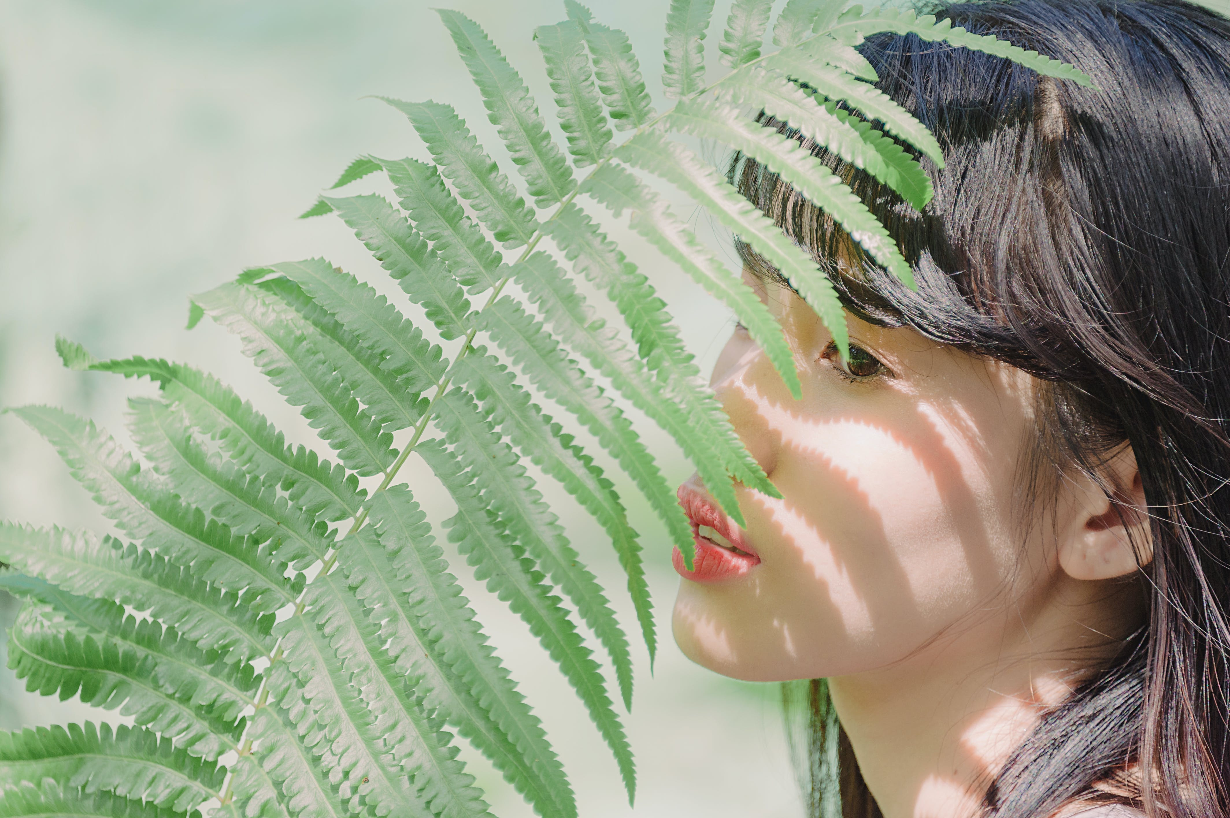 Close-Up Photography of Woman Near Fern