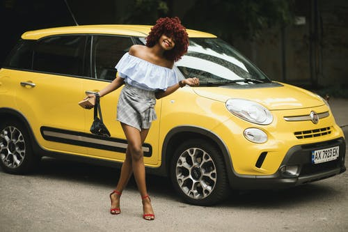 Woman Standing Near Yellow Fiat 500L