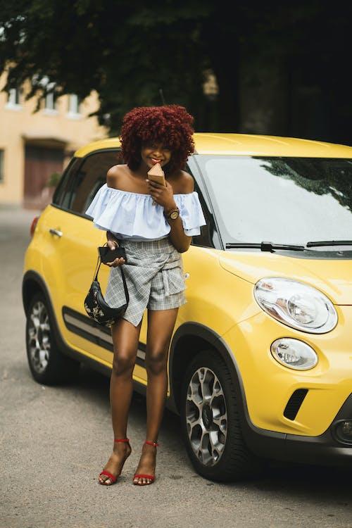 Woman Standing Beside Yellow Fiat 500l