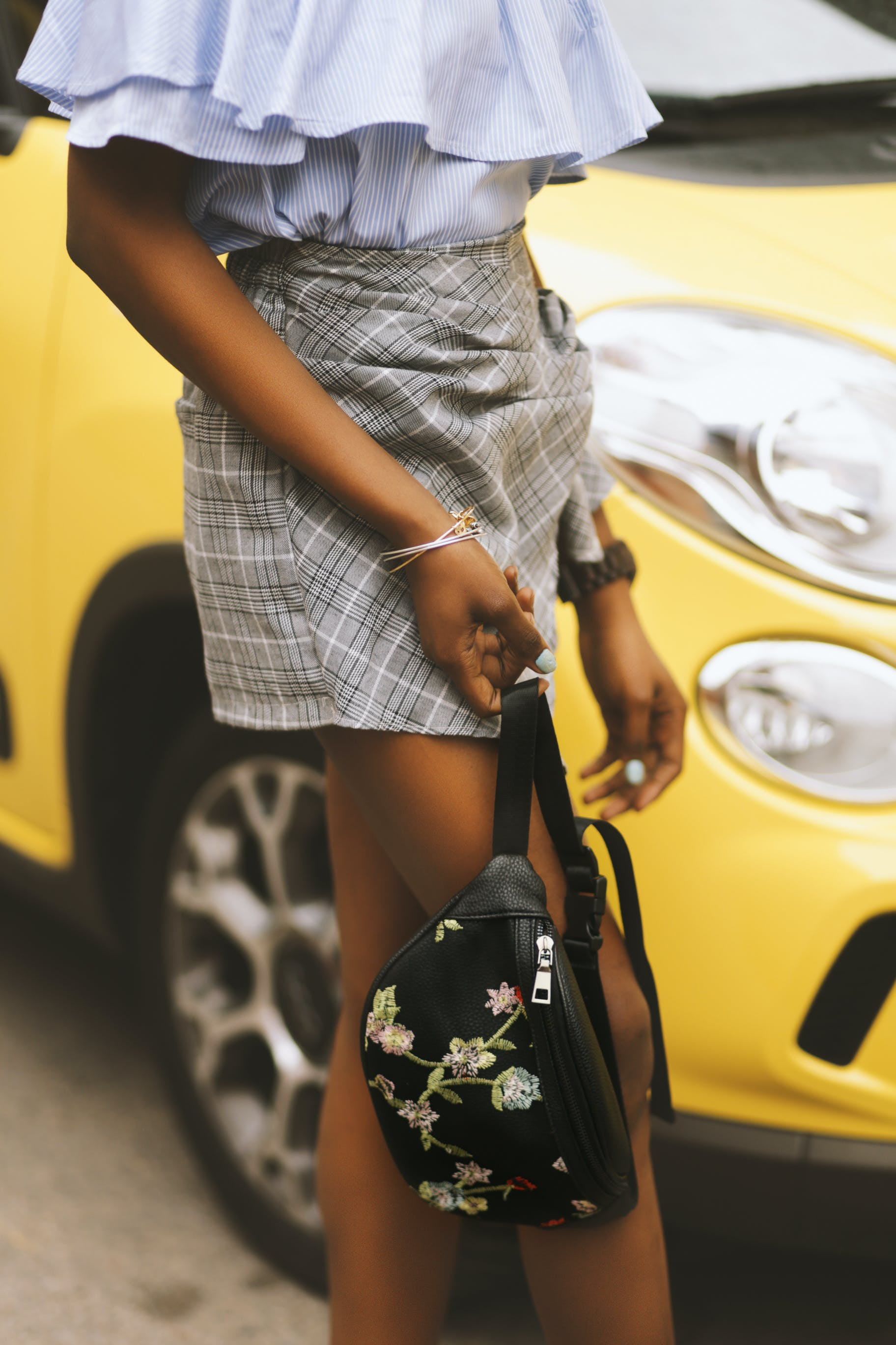 Woman Holding Black Leather Bag Standing Near Yellow Vehicle
