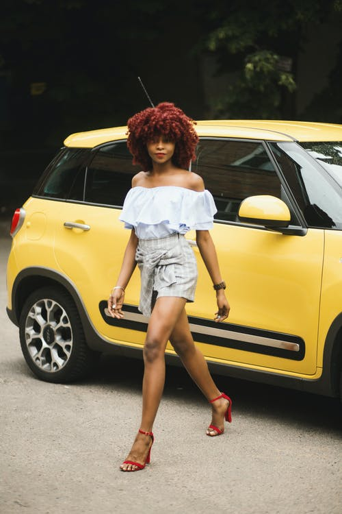 Woman Wearing White Off-shoulder Blouse Standing Next To Yellow Fiat 500l