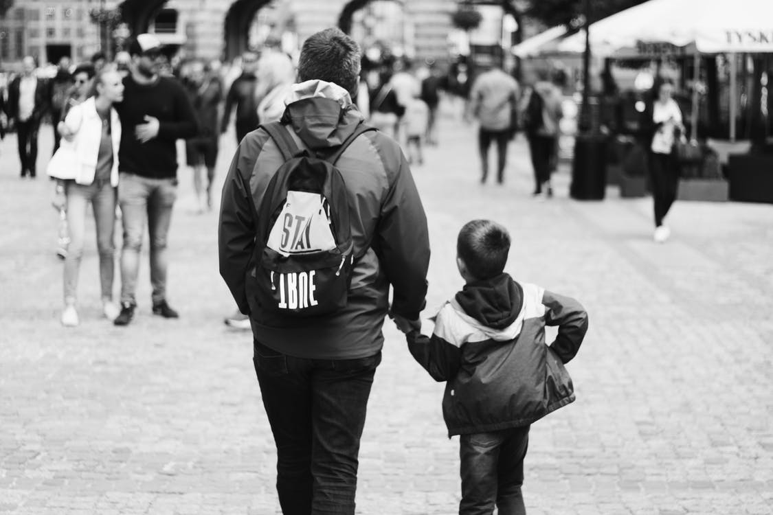 Grayscale Photography of Boy Holding Hand of Man