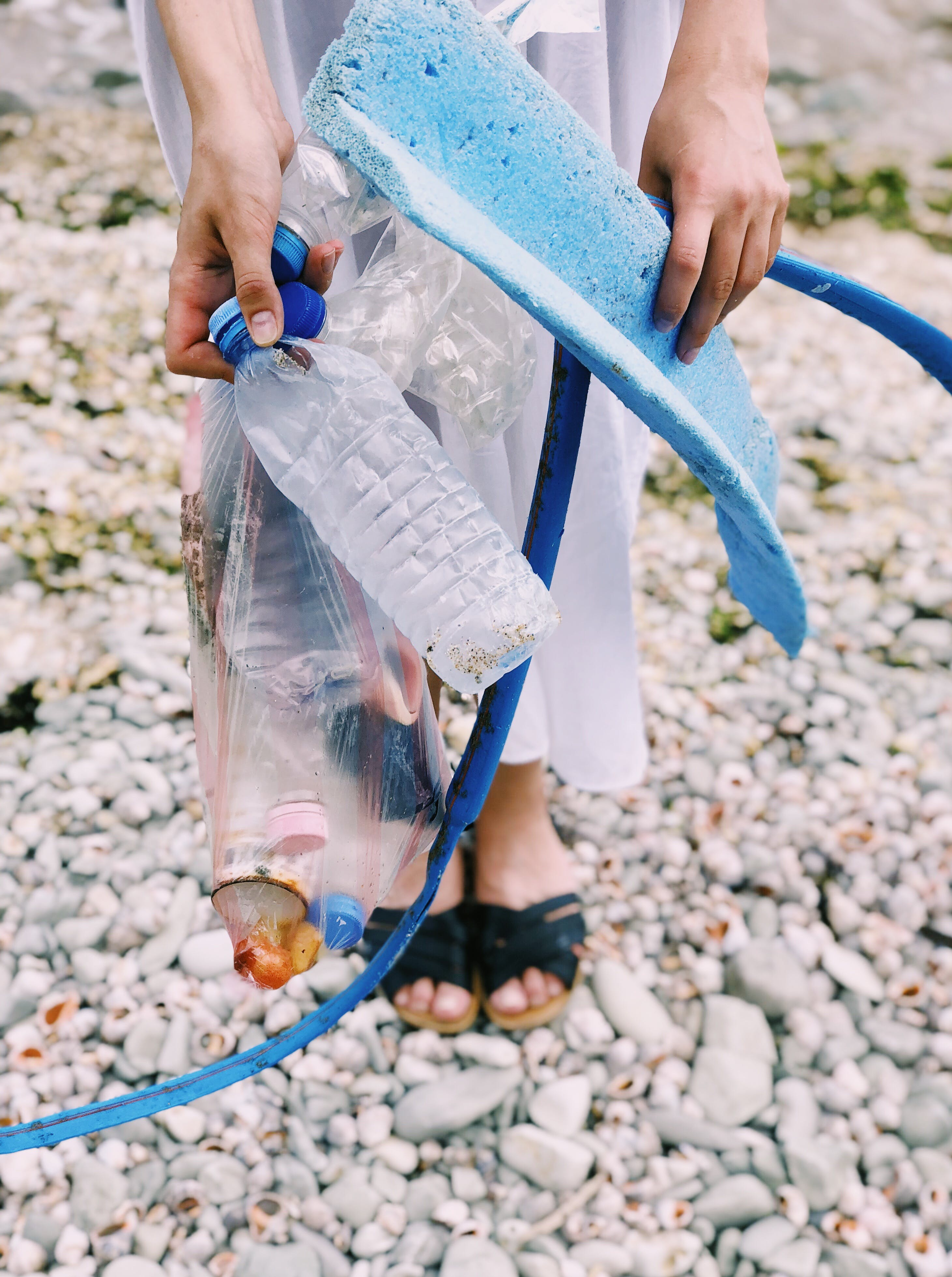 Person Holding Plastic Bottles and Hose