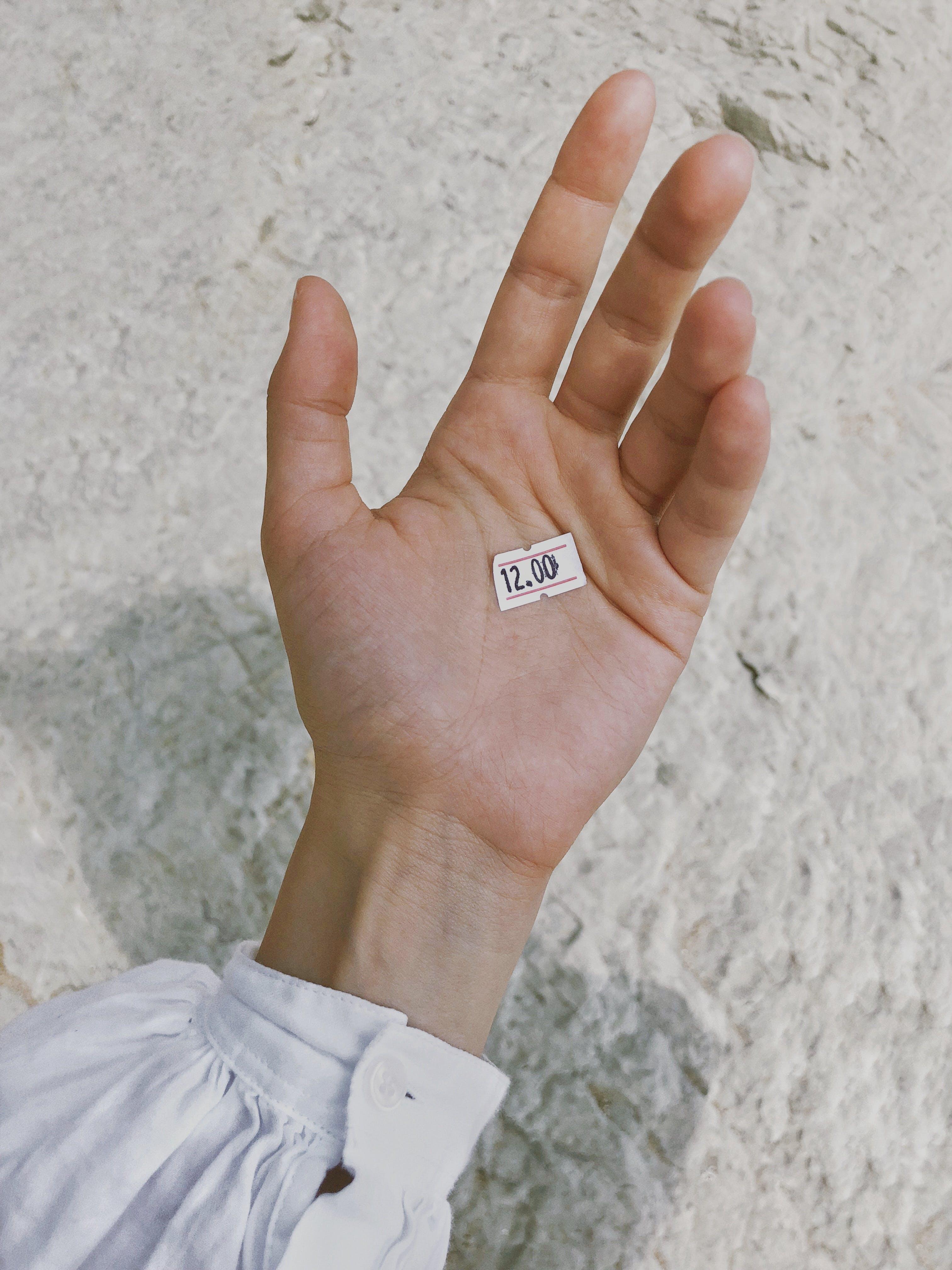 White Price Tag on Human Palm