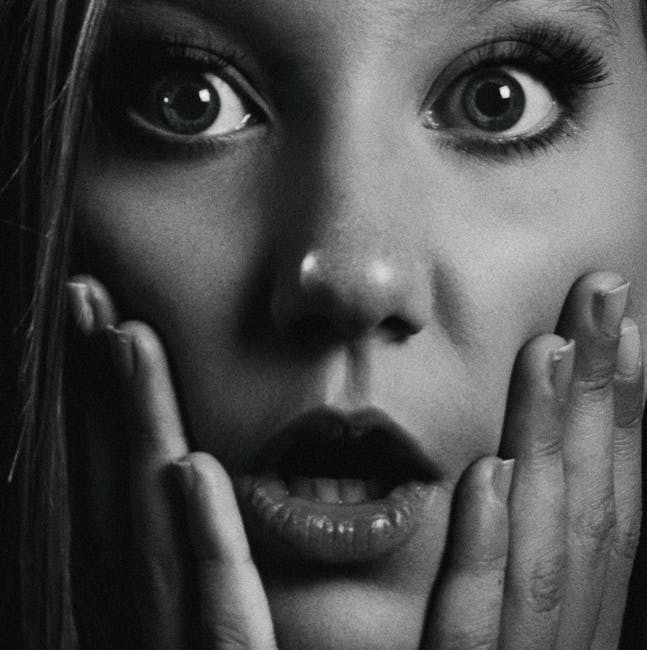 Grayscale Photo of Woman Holding Her Face