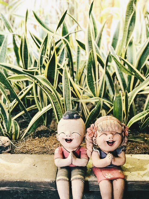 Boy and Girl Figurine Near Snake Plants at Daytime