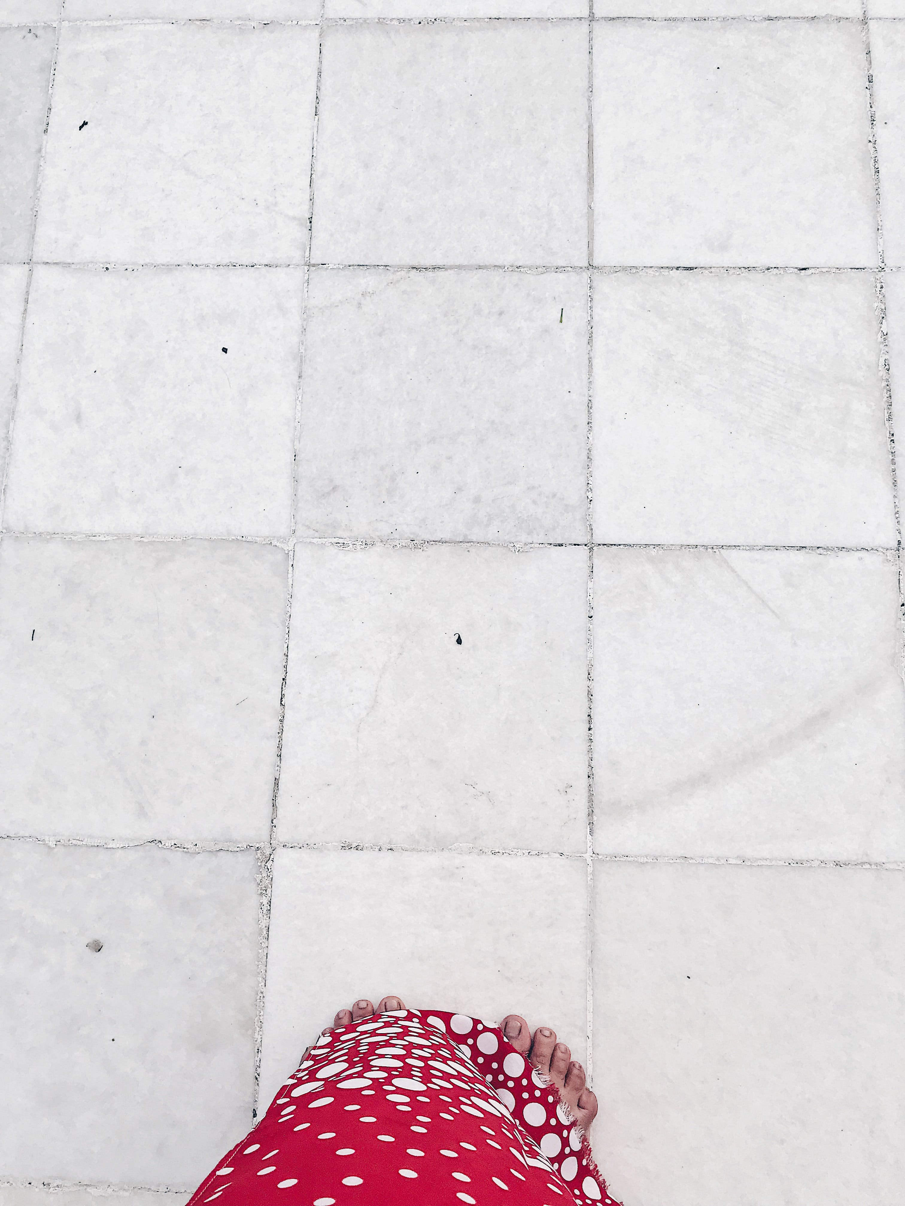 Person Stepping on White Floor Tile