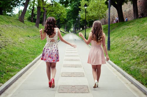 Two Women Walking On Pathway