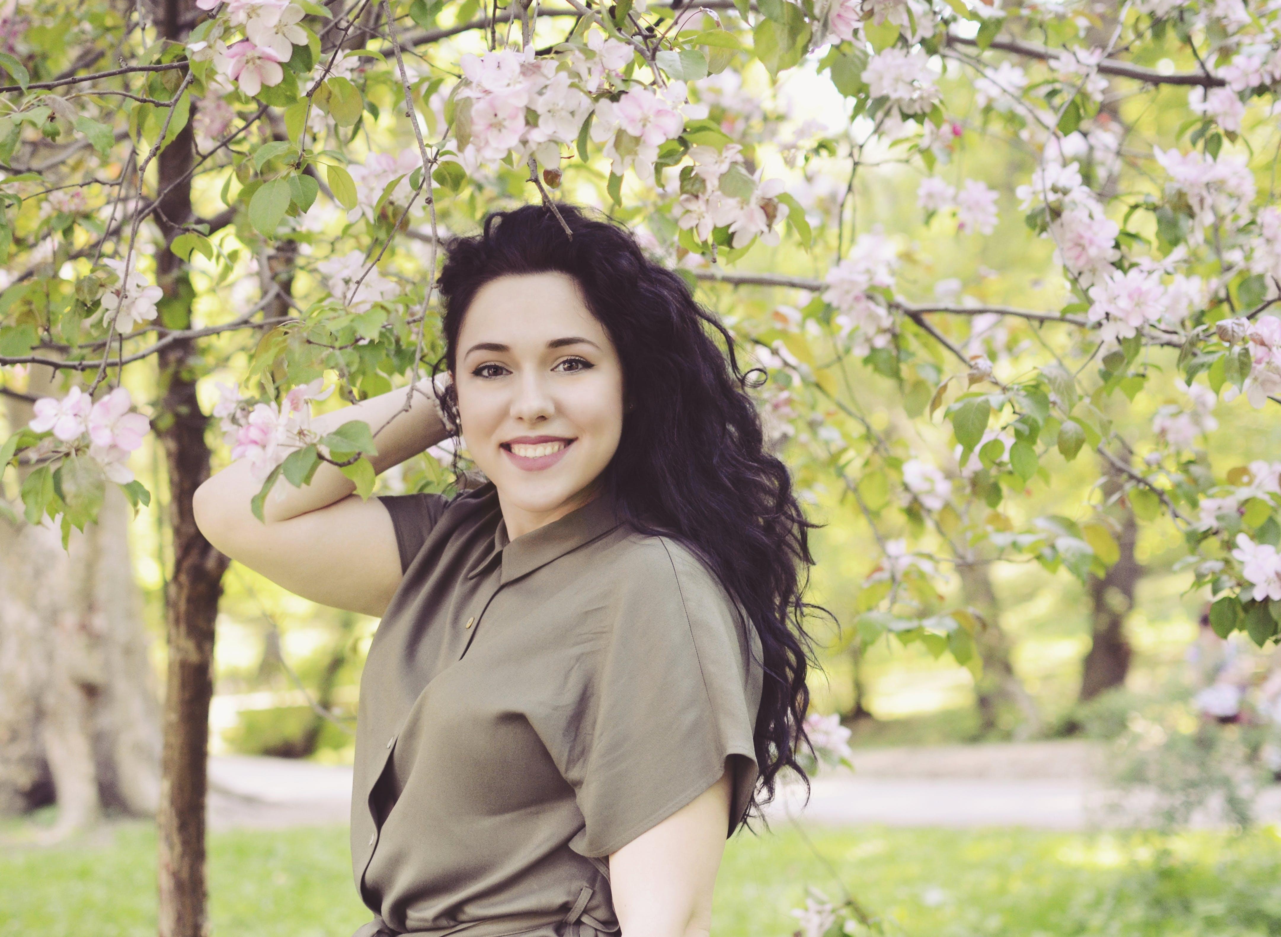 Woman Holding Her Hair Near Flowering Tree