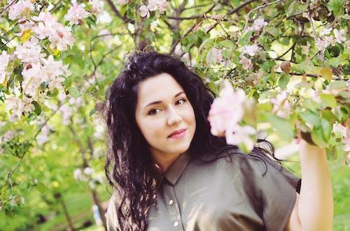 Foto d'estoc gratuïta de cabells castanys, cabells llargs, flors roses, parc