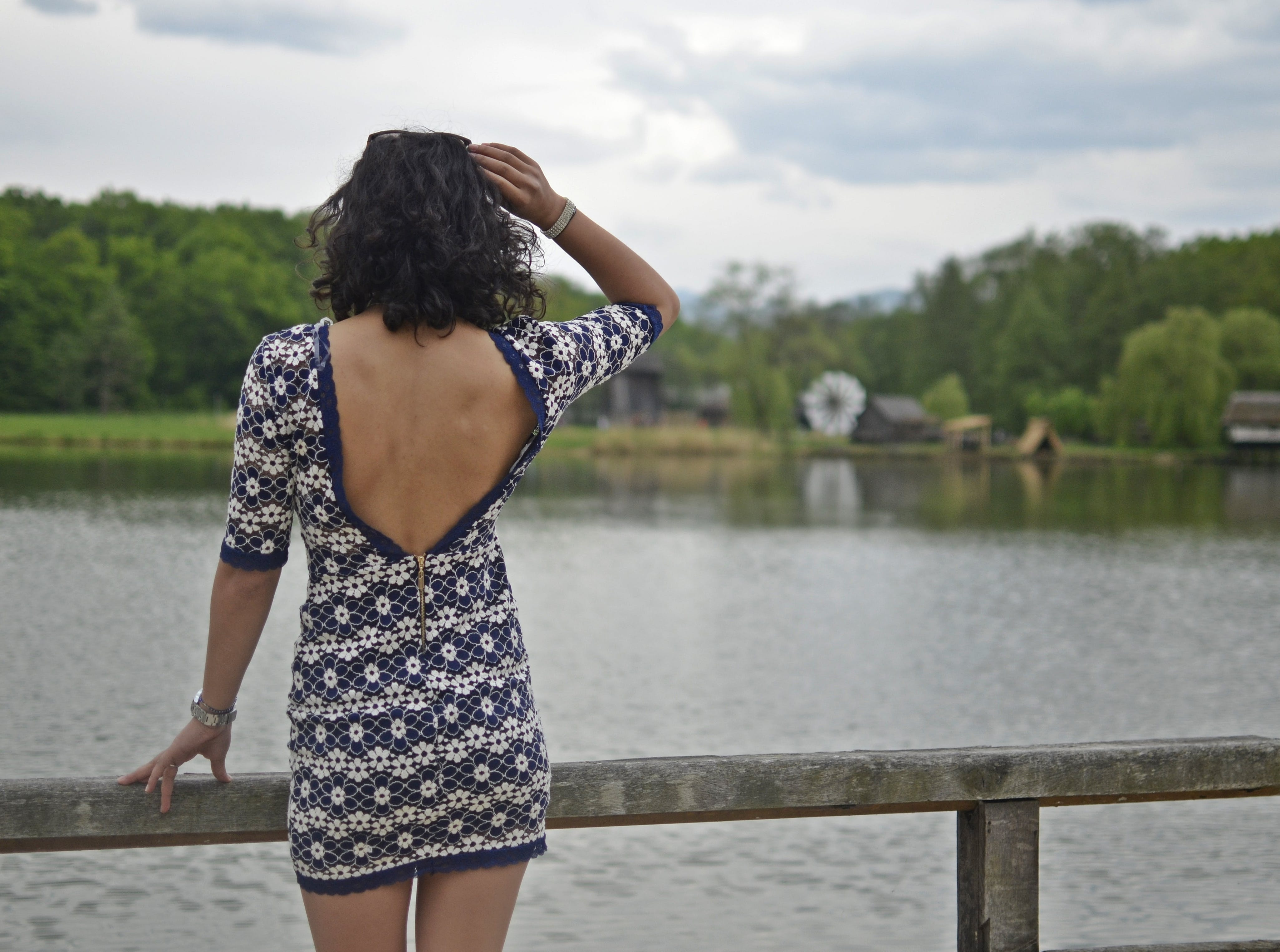 Woman in Front of Lake Under Cloudy Sky