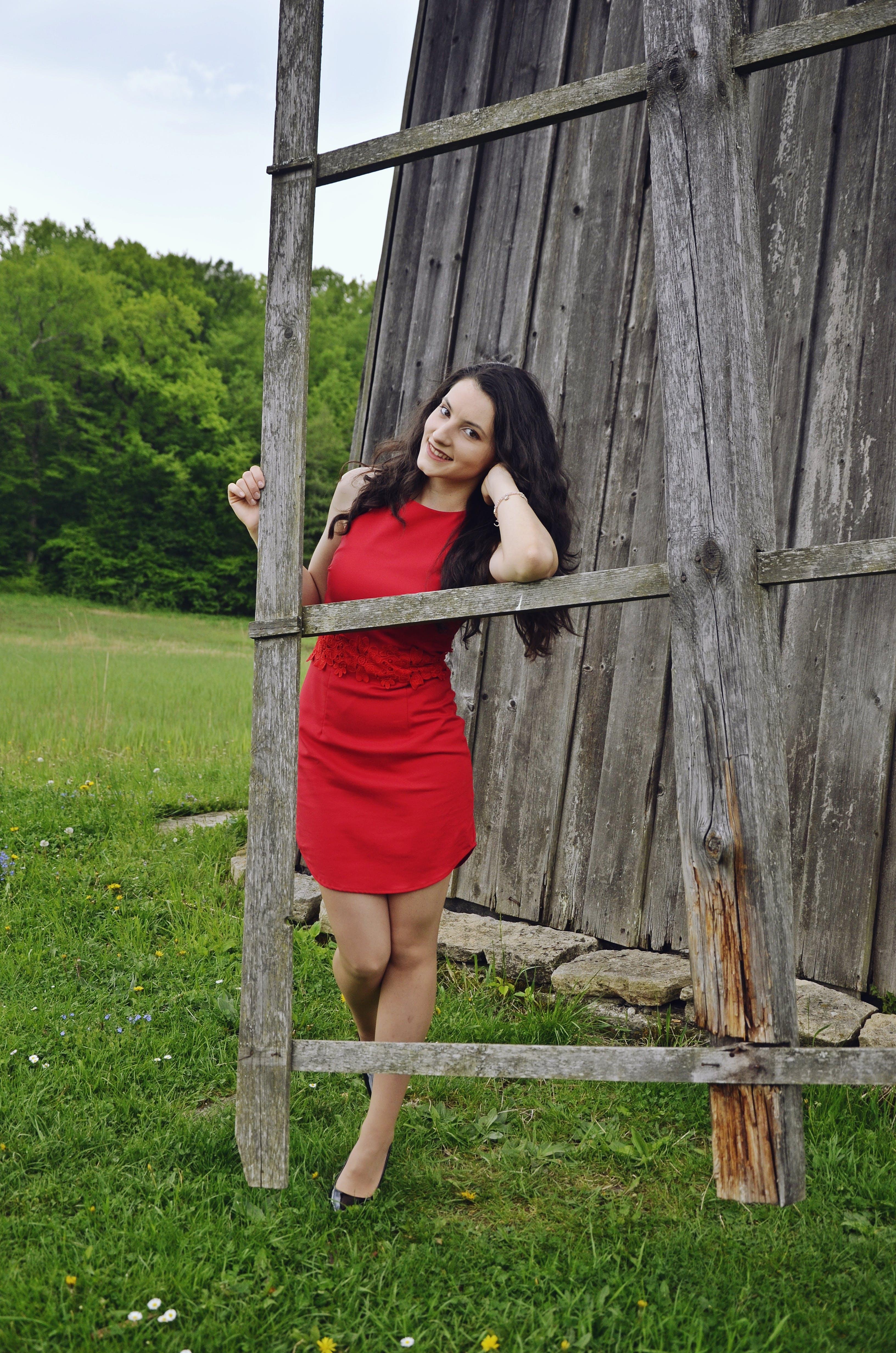 Woman in Red Dress Standing Beside Windmill