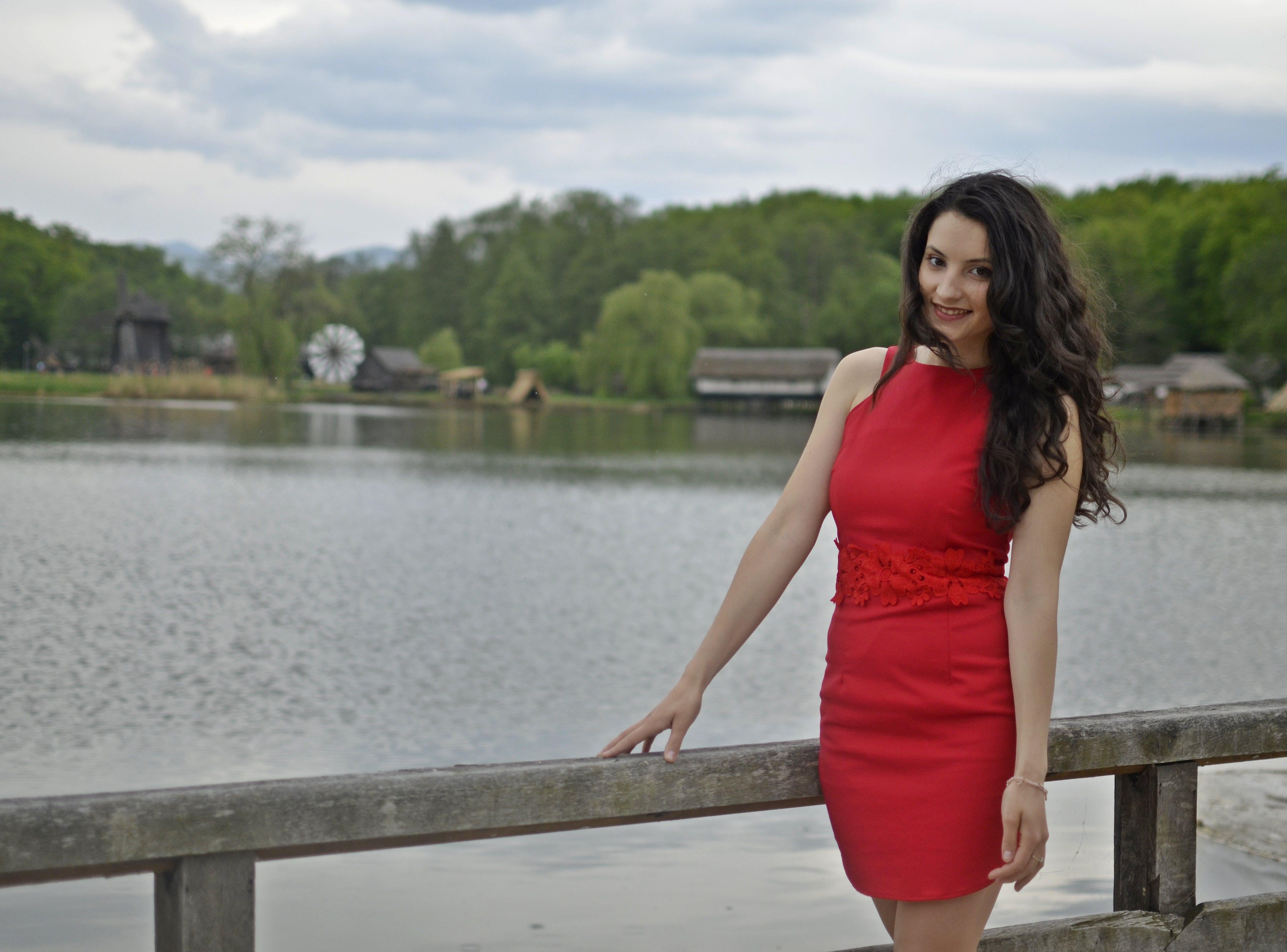 Woman Leaning on Bridge Bar Near Body of Water