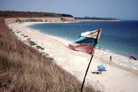 Blue Ocean Near on White Sands With White Blue and Red Flag on Shore