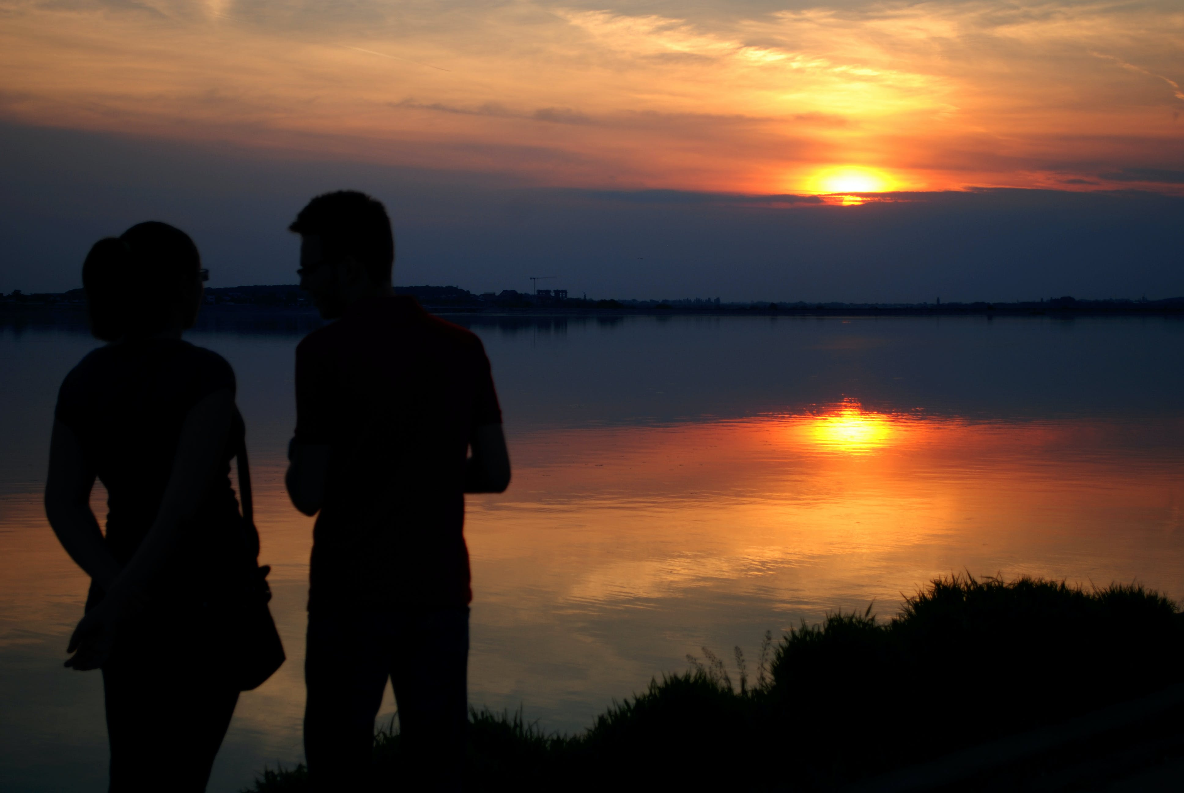 Silhouette of Man and Woman Near Water during Sun Set