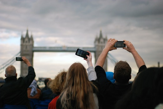 People Taking Picture at Tower Bridge Under Gray Clouds