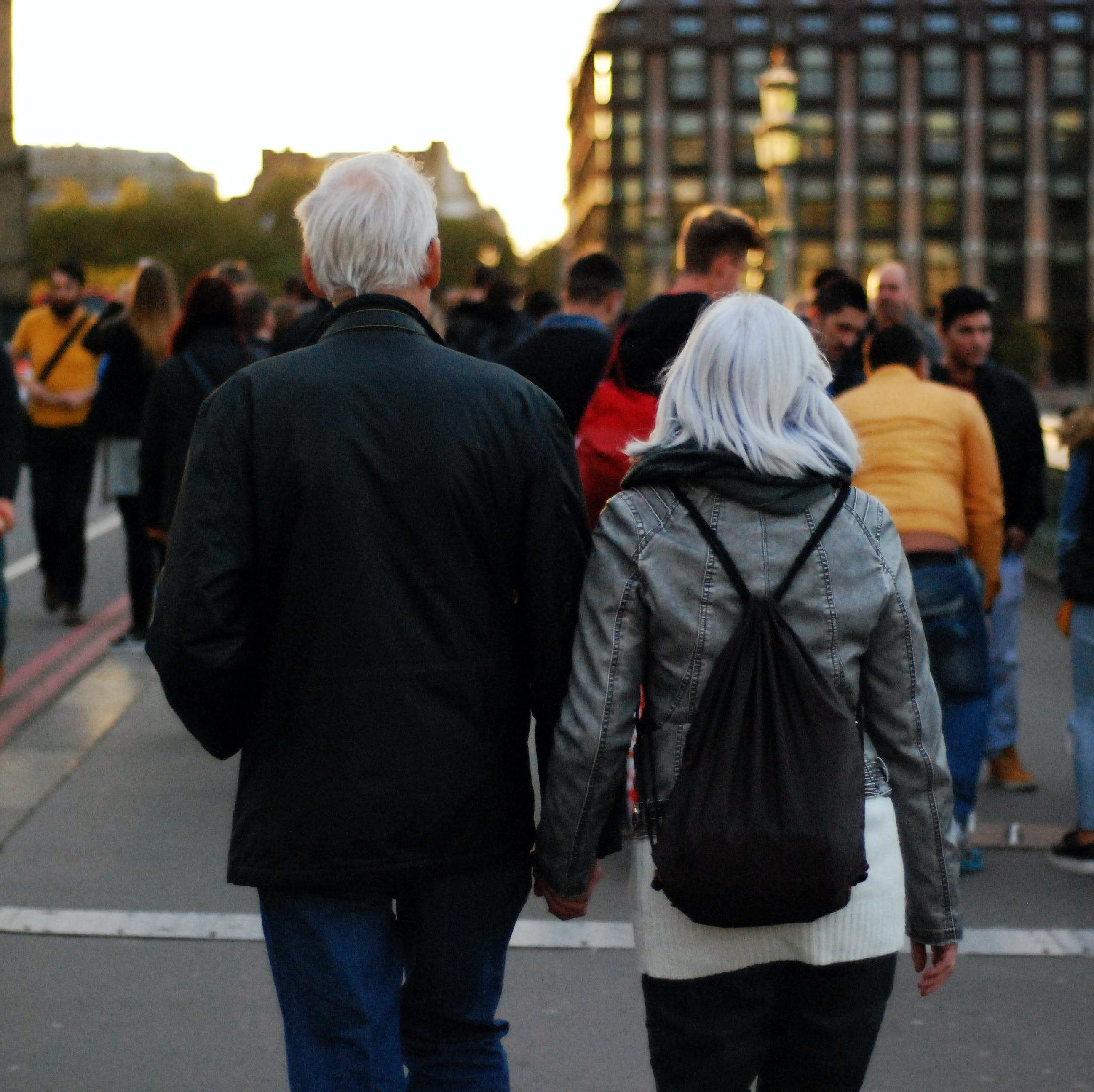Man in Black Jacket Beside Woman in Grey Leather Jacket Holding Hands at Dusk in Busy Street