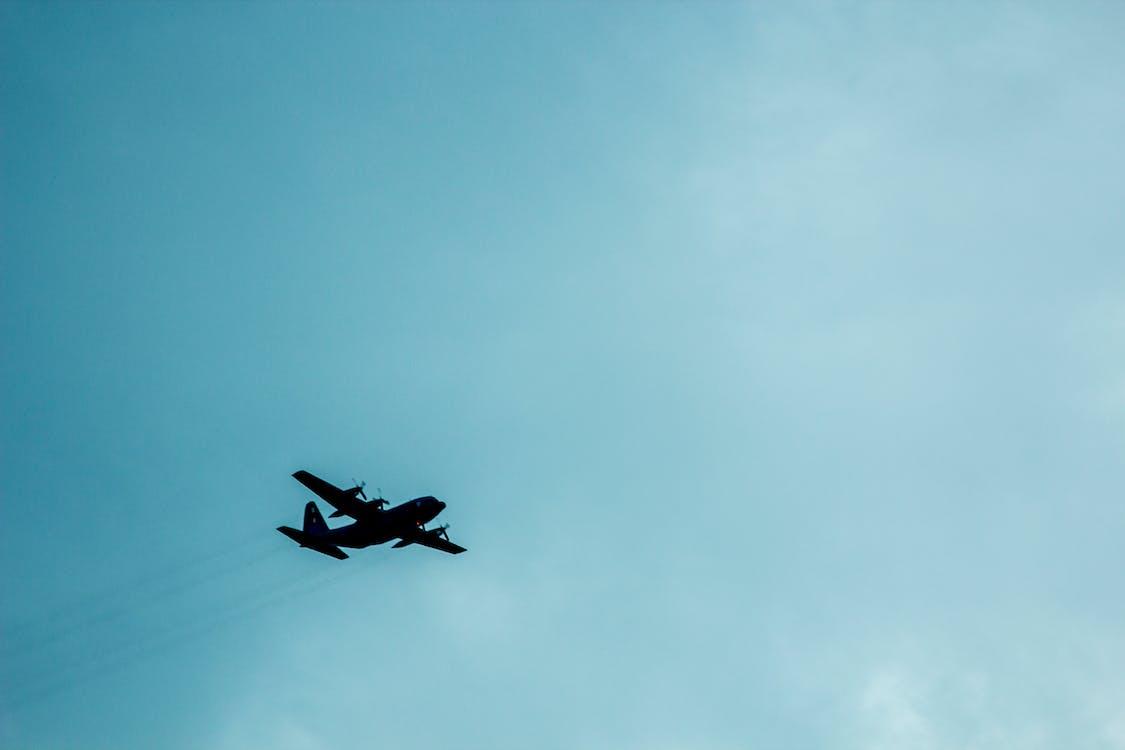 Airplane Against Blue Cloudy Sky Overhead