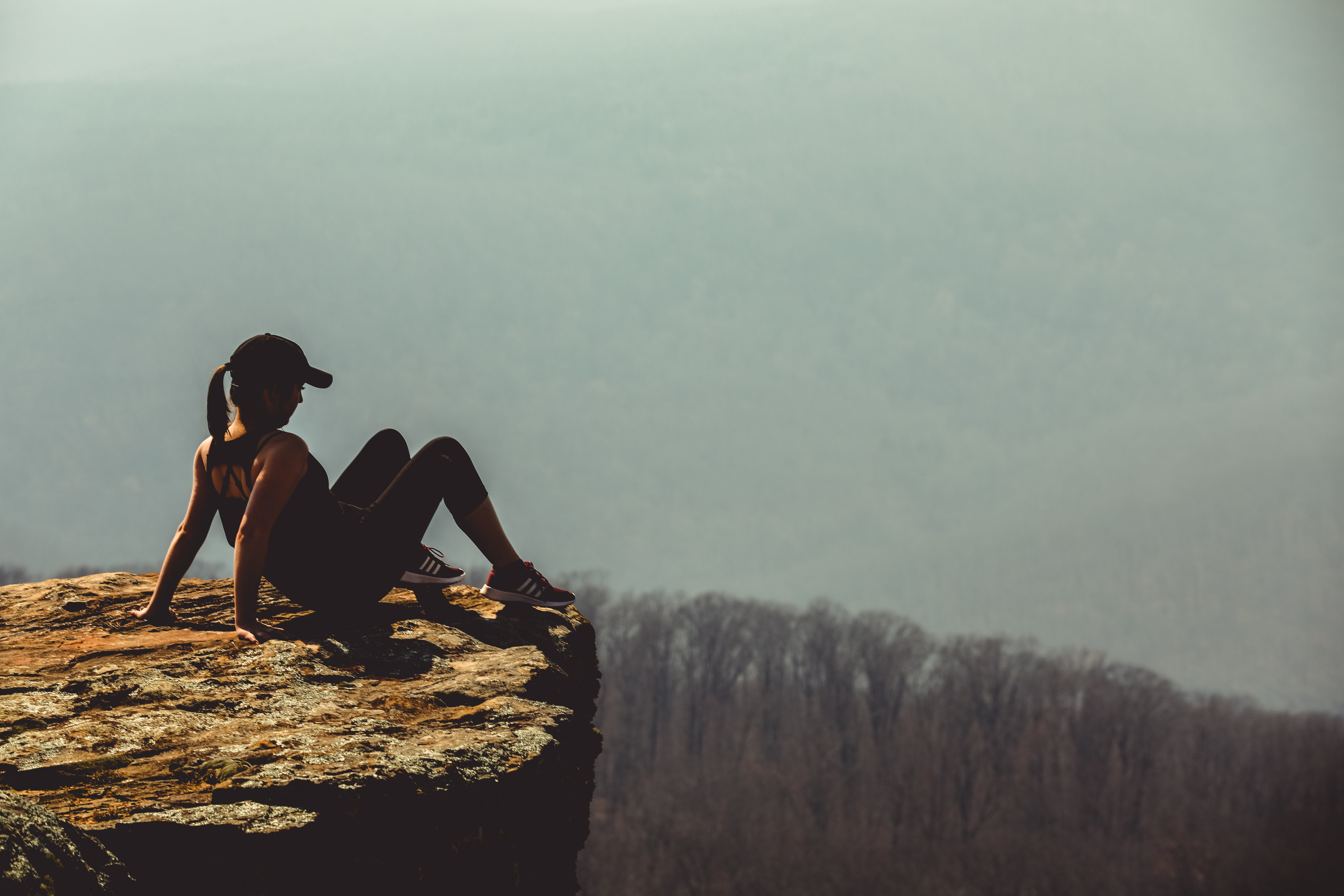 Shallow Focus Photography of Woman on Rock Formation