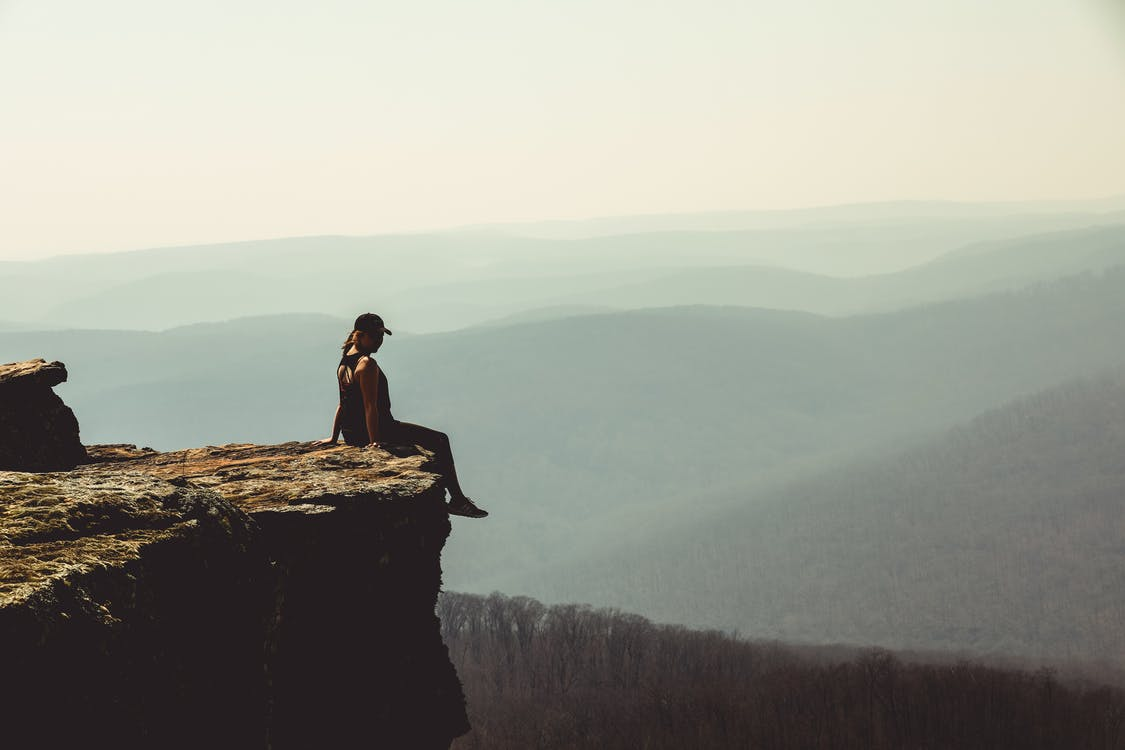 Woman Sitting on Edge of Rock Formation