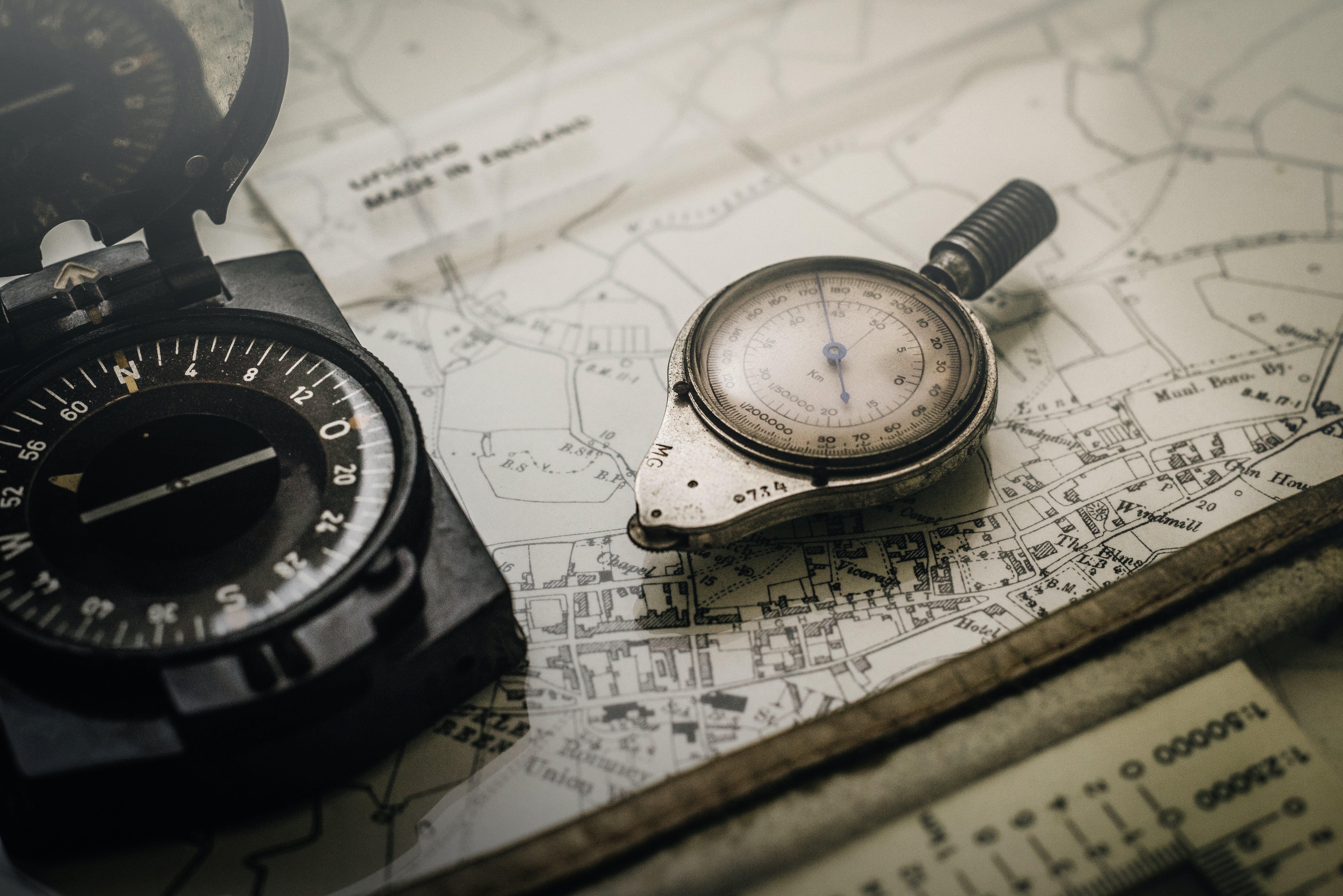 Shallow Focus Photography of Black and Silver Compasses on Top of Map