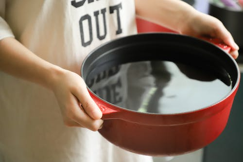 Person Holding Red Pot Filled with Water
