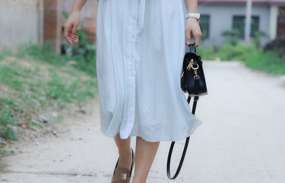 Woman Holding Black Leather Bag Walking on Road