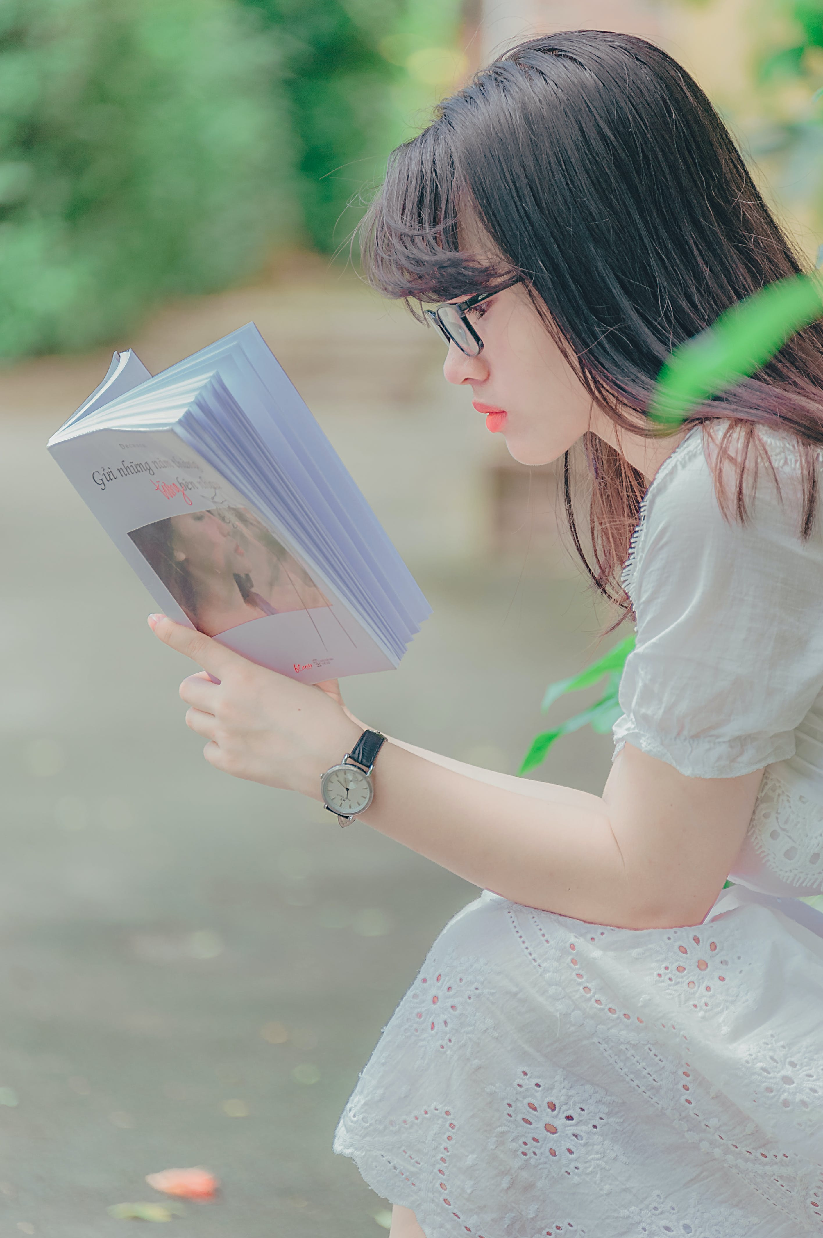 Woman Sitting While Reading Book Outdoors