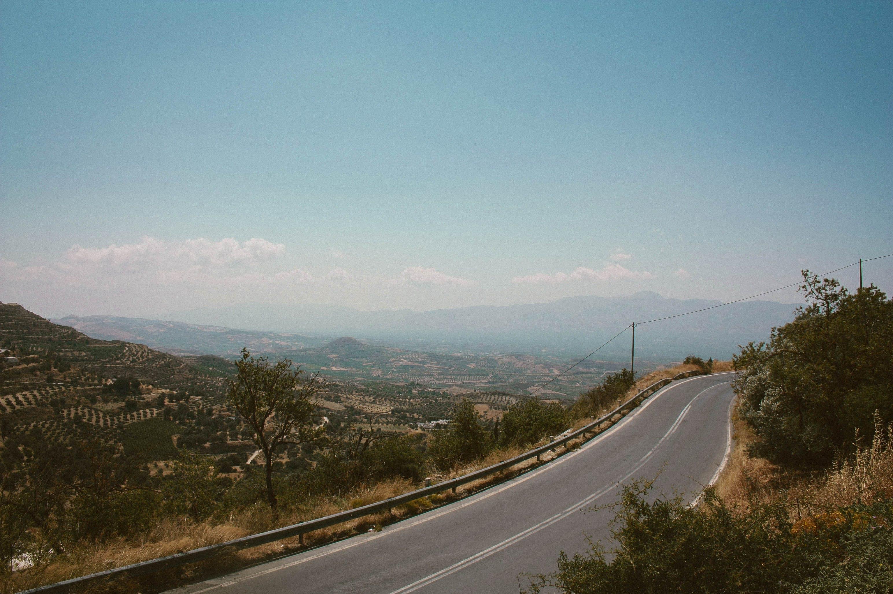 Road Between Grass Under Blue Skies
