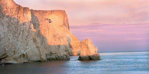 Fotos de stock gratuitas de acantilados, mar, playa, puesta de sol