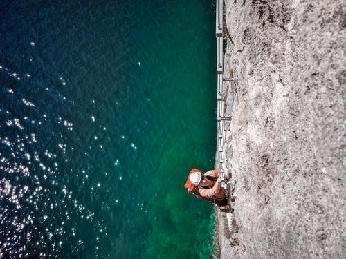 Man Wall Climbing Near Body of Water