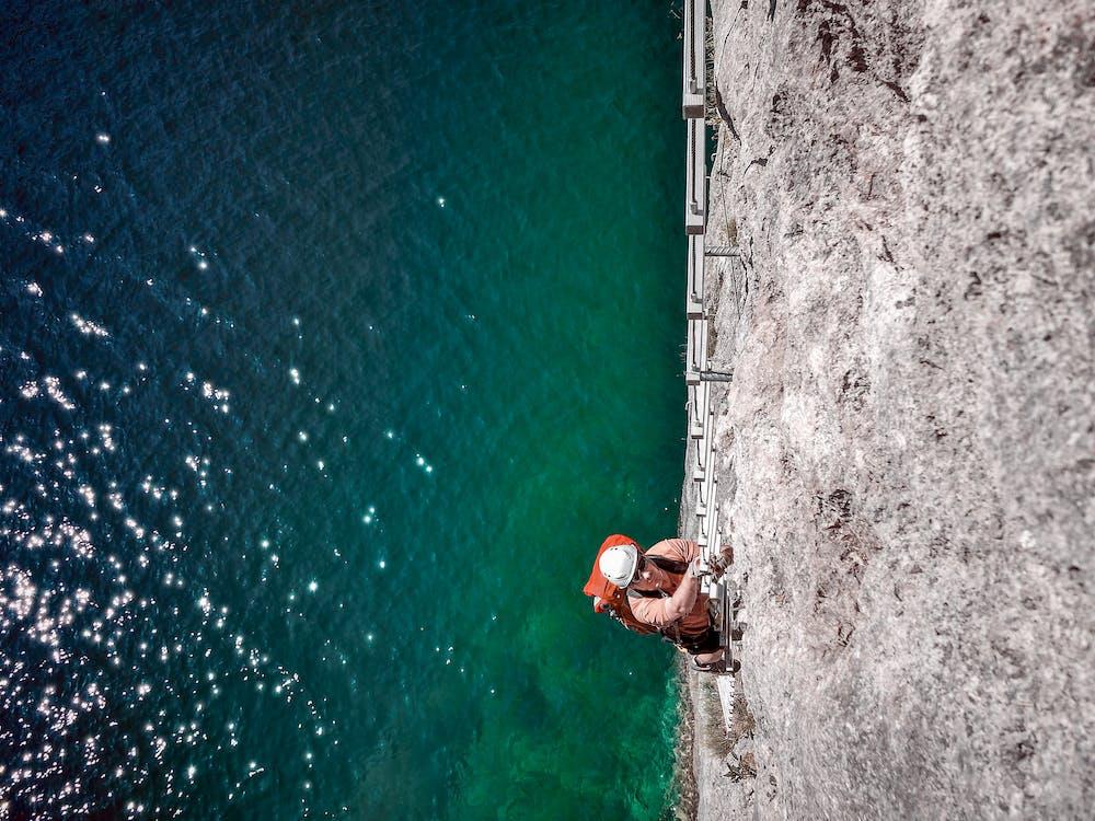 Man Wall Climbing Near Body of Water