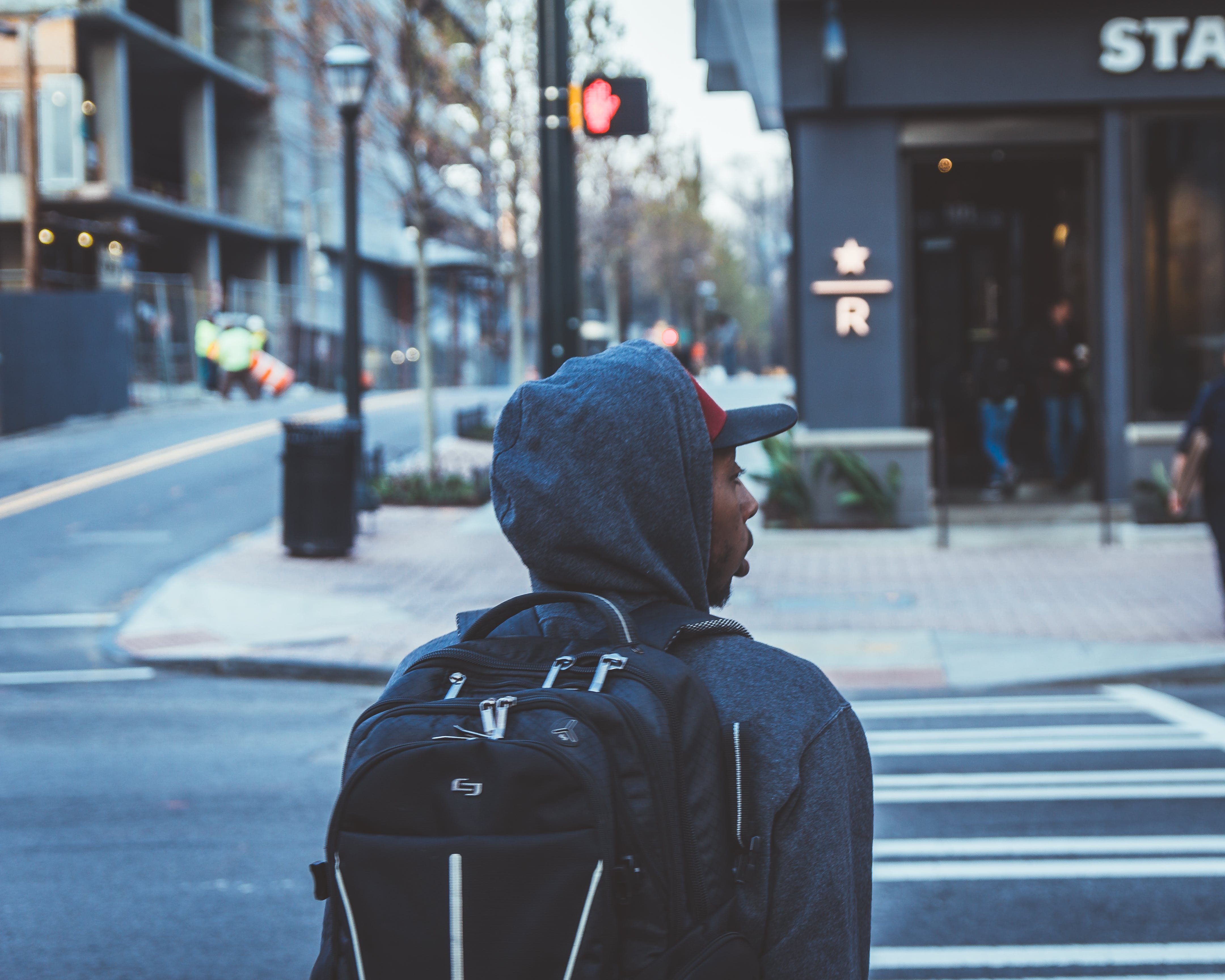 Person Wearing Black Backpack About to Cross Pedestrian