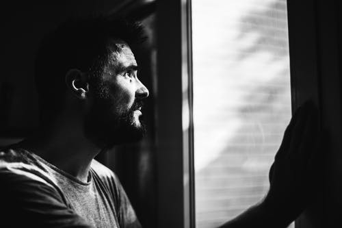 Greyscale Photo of Man Looking Through Window