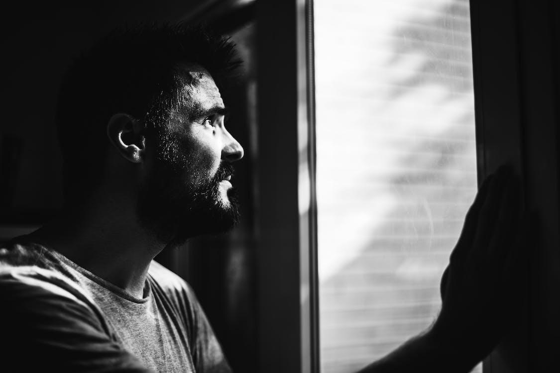Greyscale Photo of Man Looking Through Window