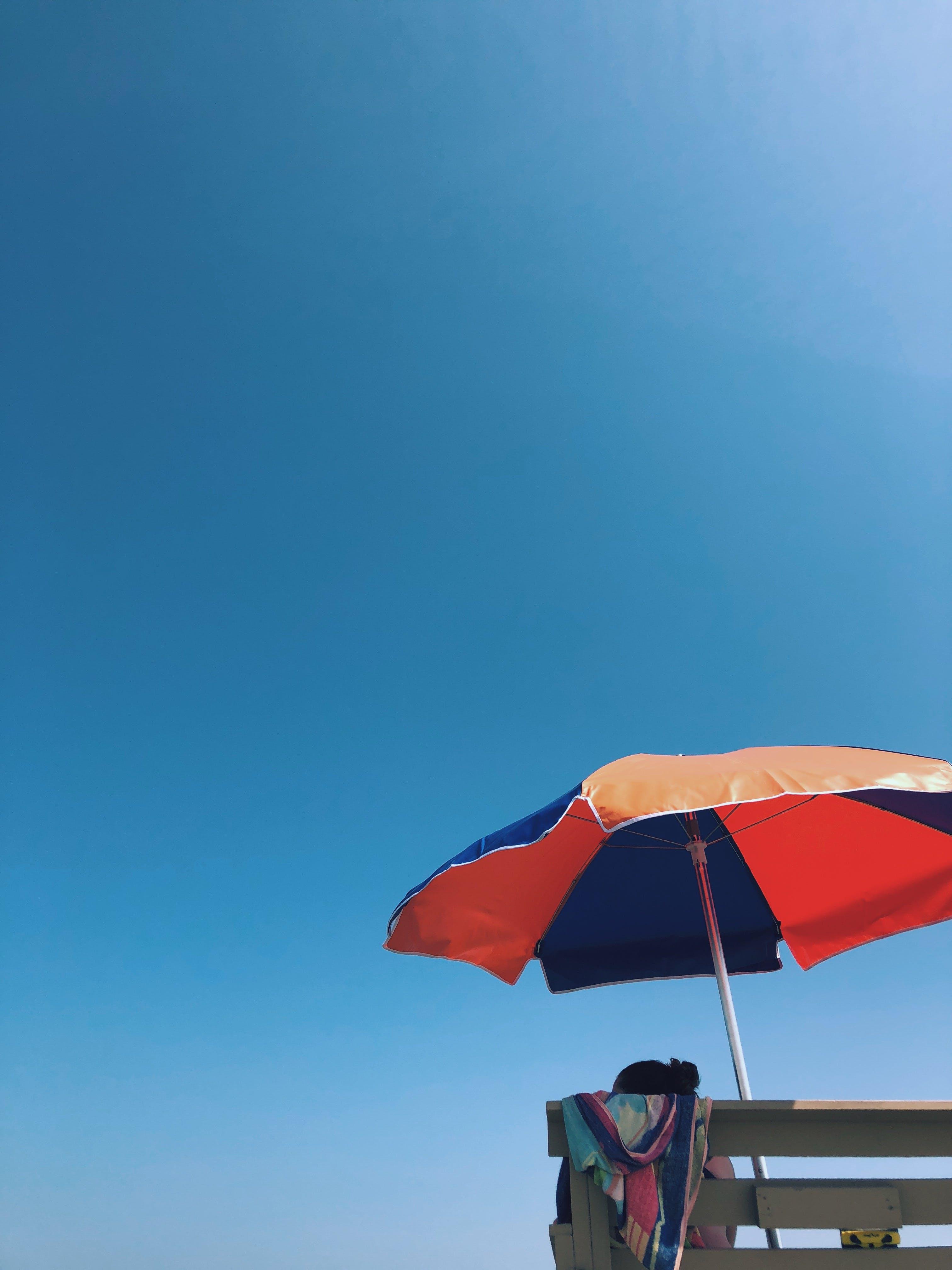 Person Sitting on Bench Under Umbrella