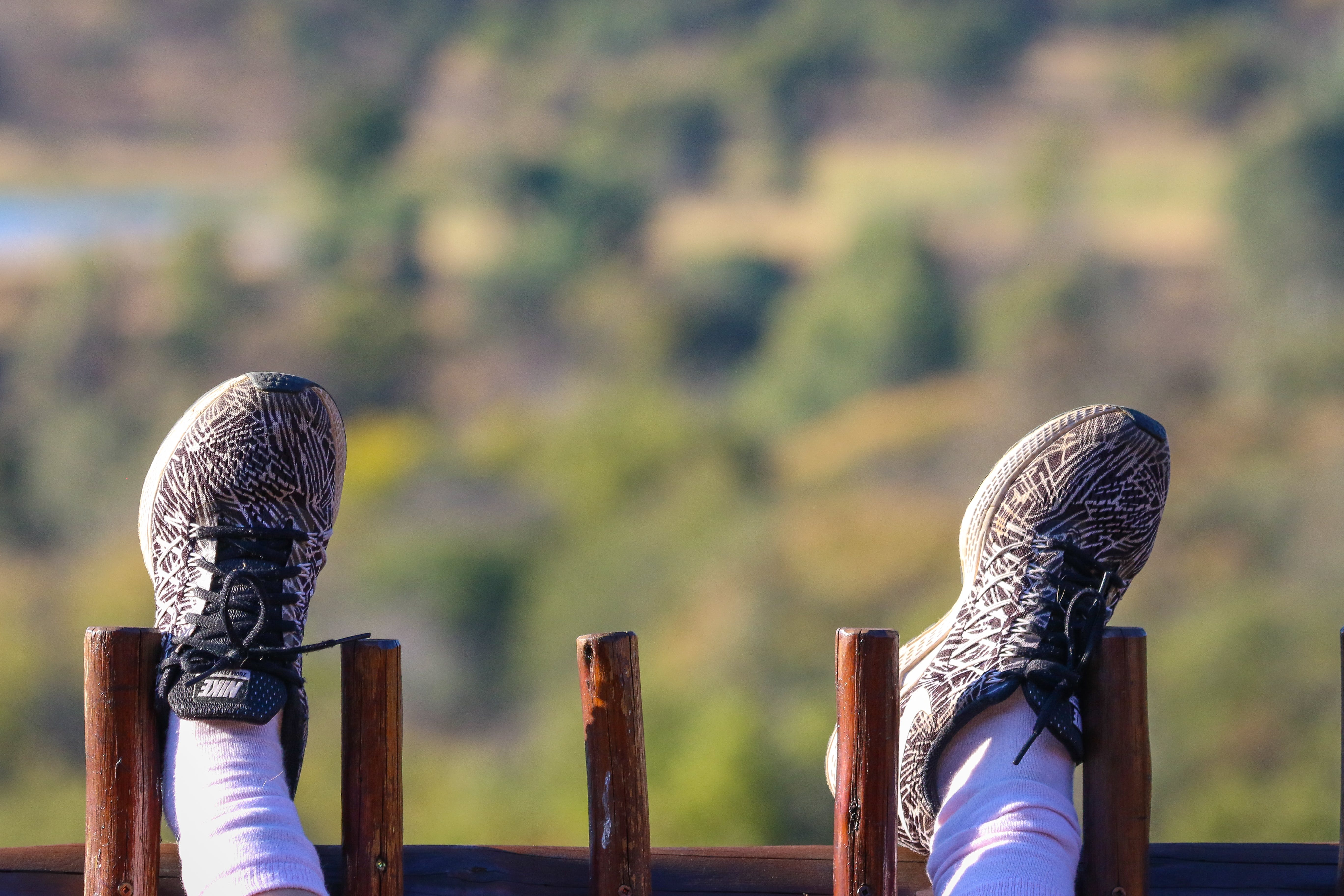 Person Wearing Black and Grey Nike Shoes Resting Feet on Wooden Fence
