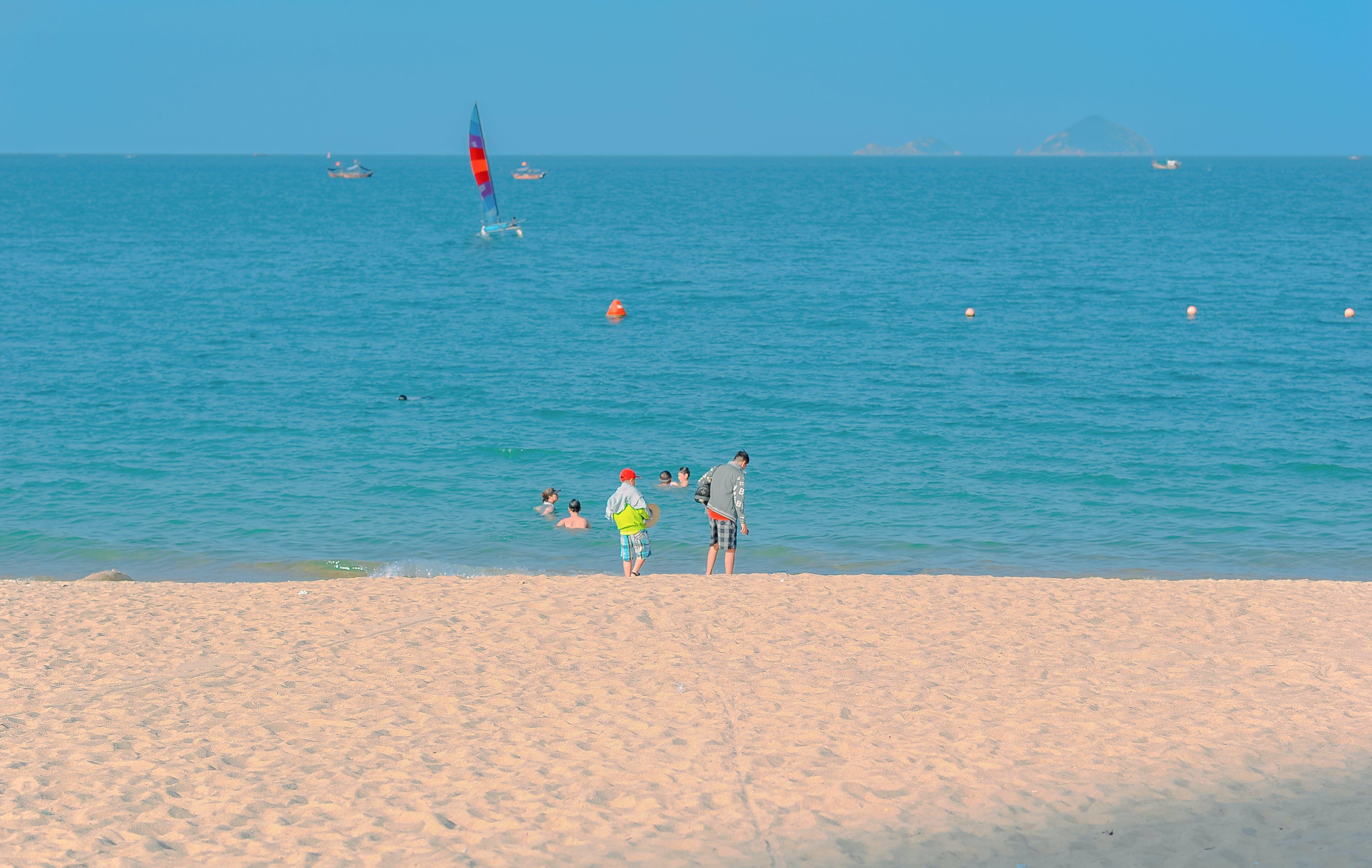 Two Kids Standing on Seashore Under Blue Sky