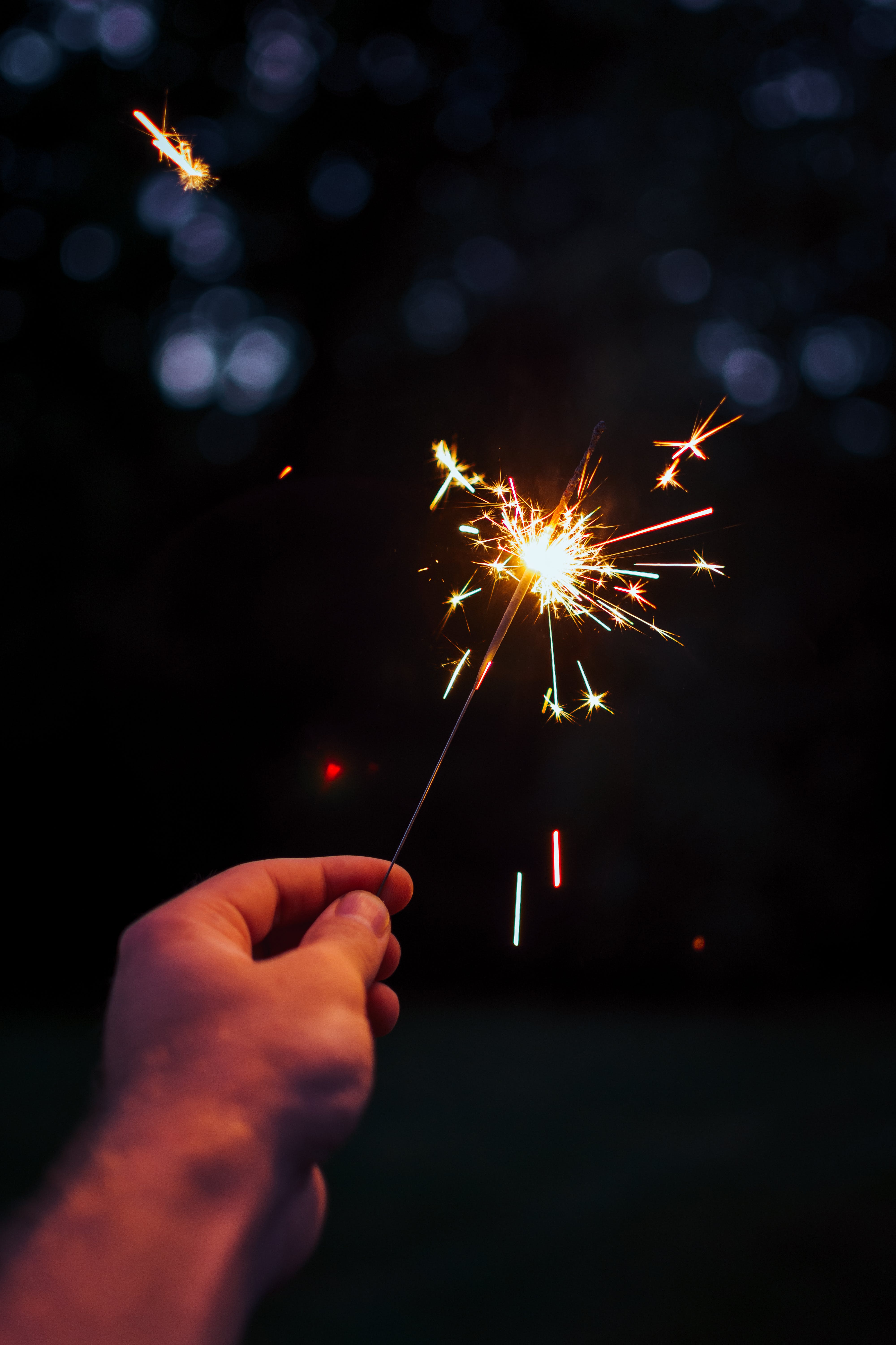 Selective Focus Photography Person Holding Lighted Sparkler at Nighttime