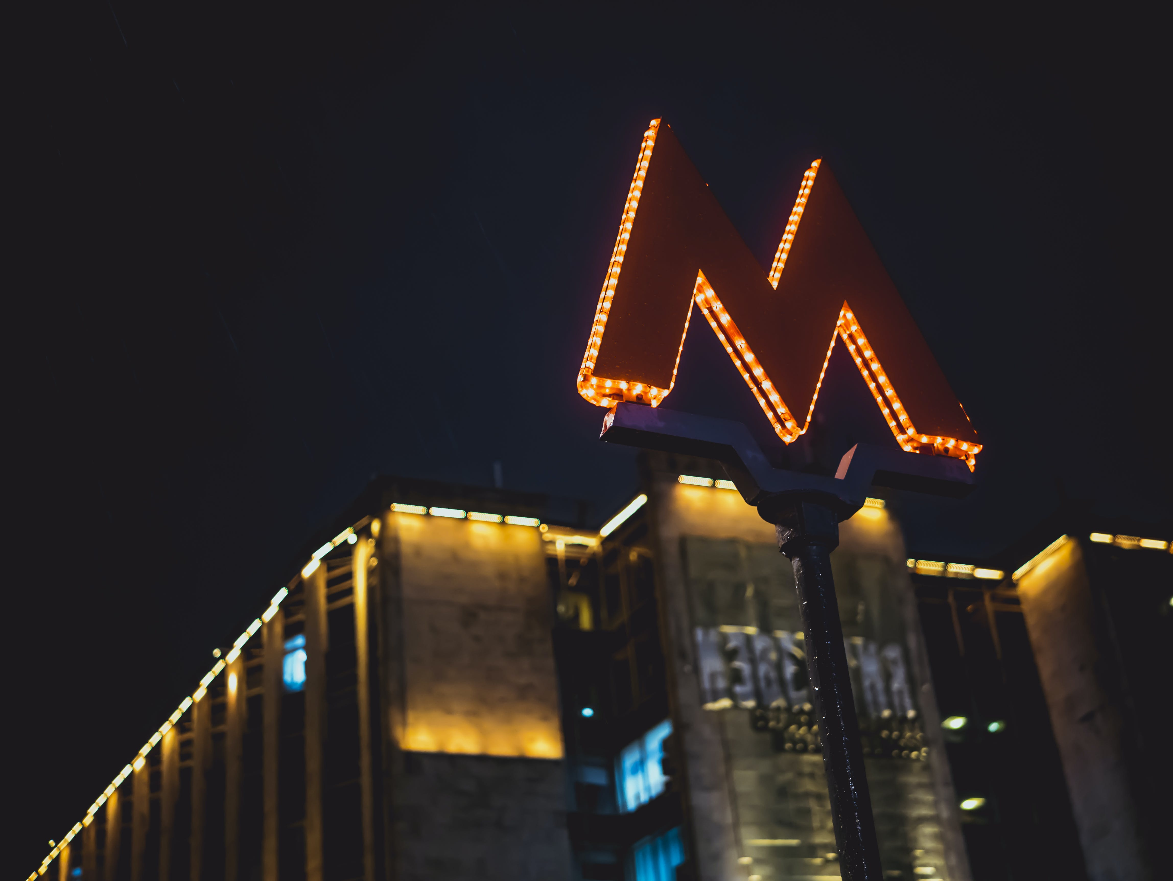Low Angle Photography of Lighted M Road Sign during Nighttime