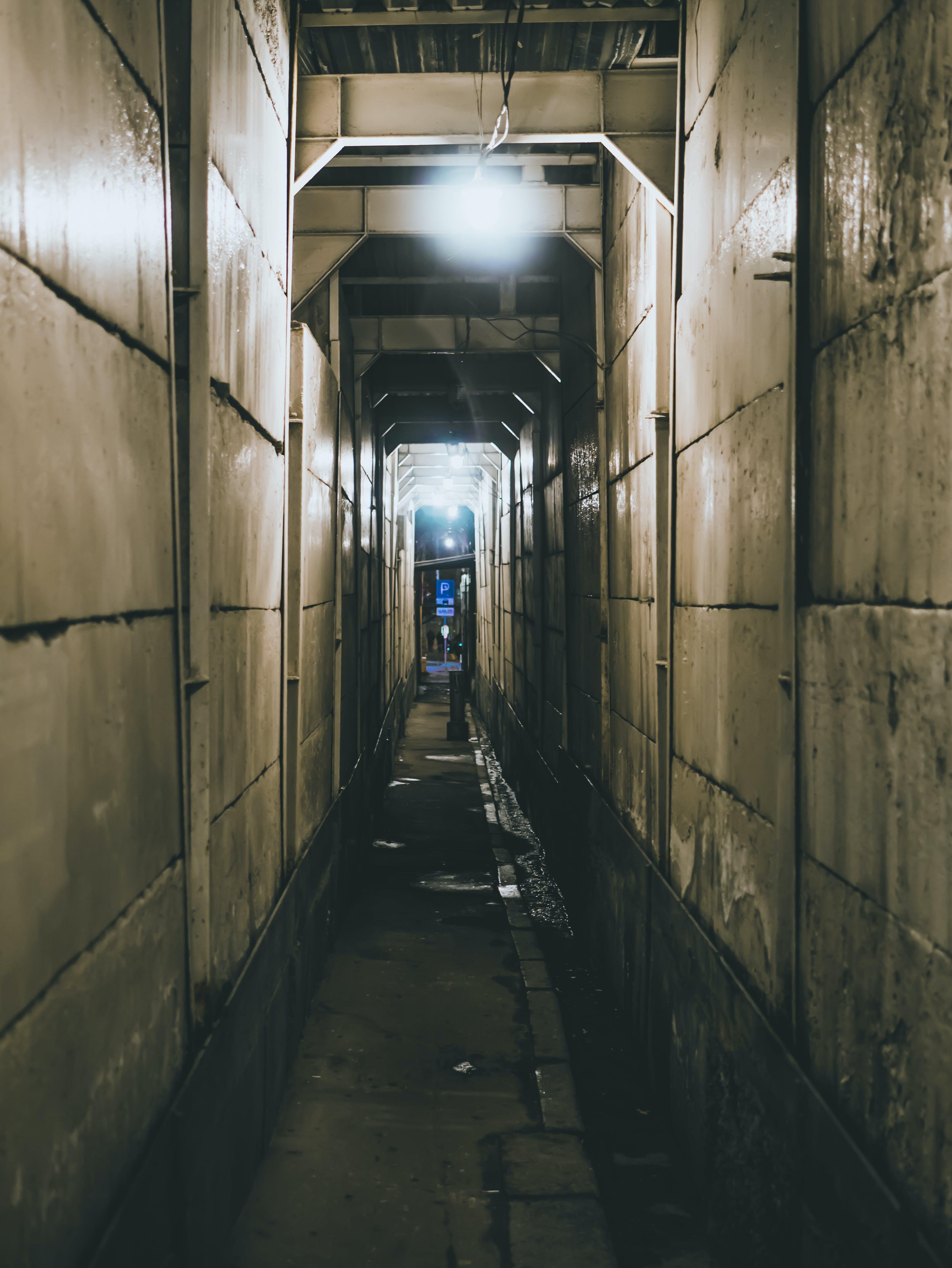 Narrow Corridor With White Light Bulb on Top